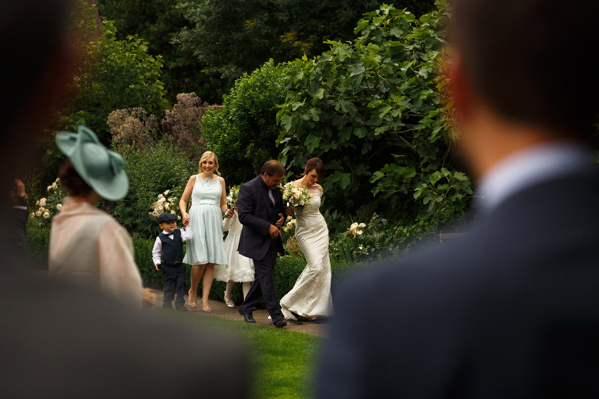 Bride making her way around the walled garden of outdoor wedding reception at Wedding guests laughing enjoying drinks in the long gallery at grays court York