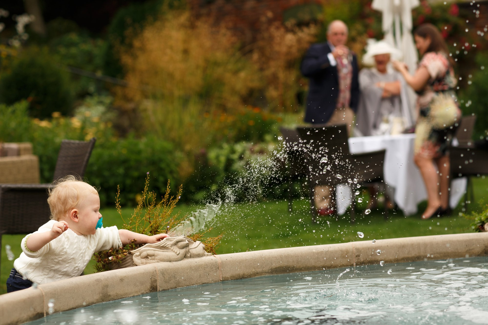 Small child playing with fountain in walled garden at grays court wedding