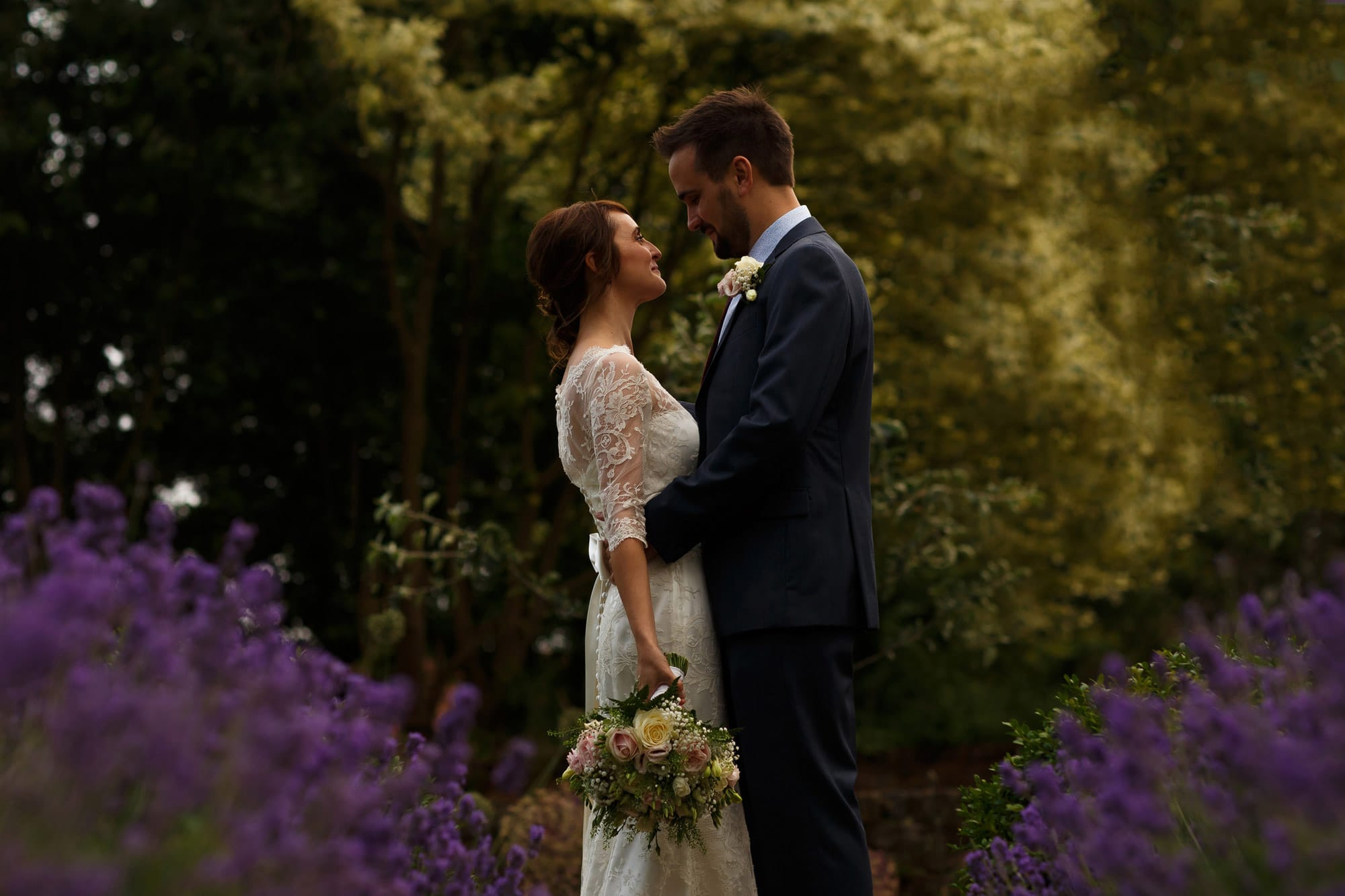 Close up portrait of bride and groom with purple flowers creating bokeh on their wedding day in the walled gardens at grays court wedding