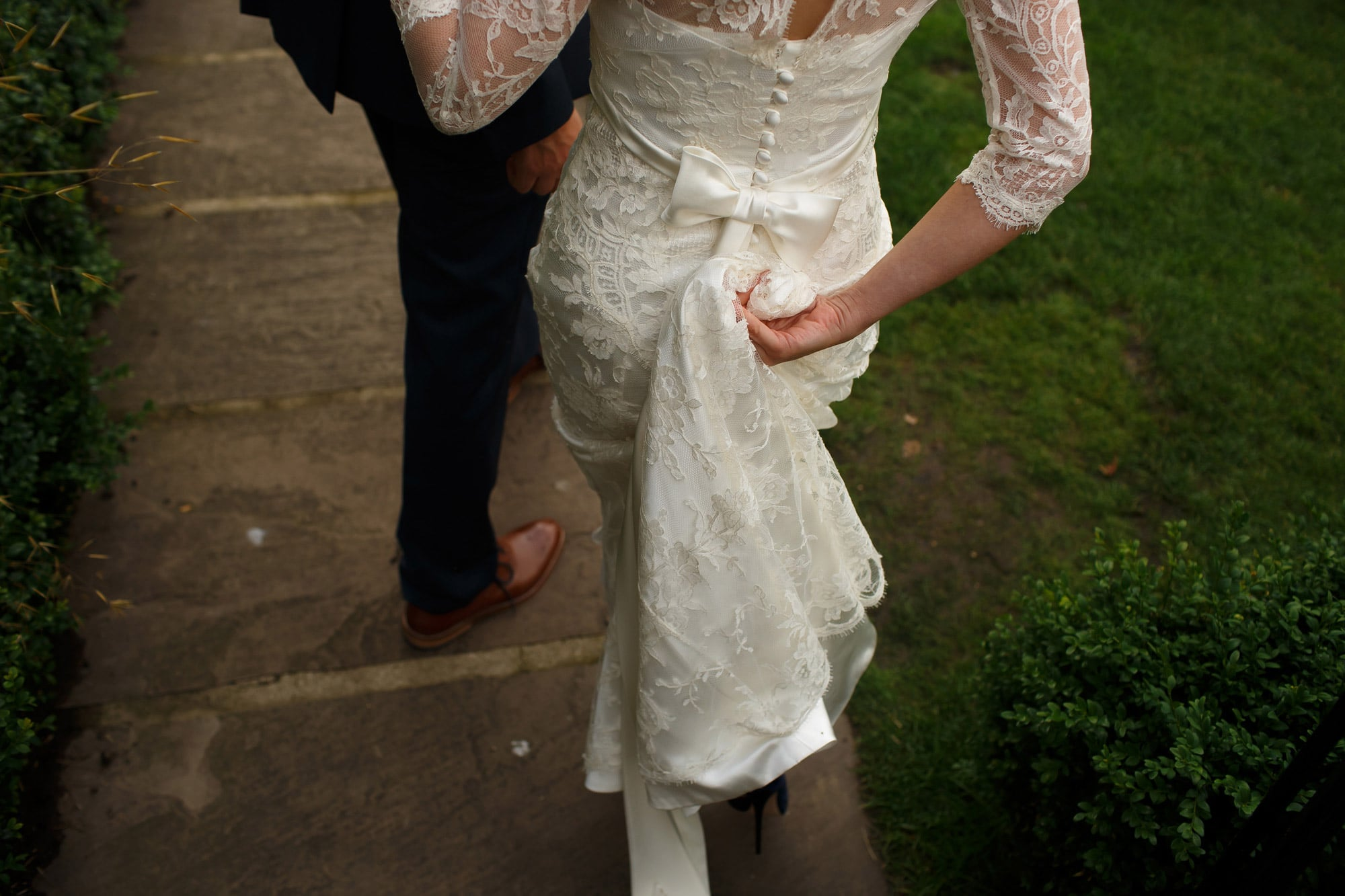 Bride wearing long sleeve Ivory lace wedding dress with bow detail holding up the train as she walks along the path of the walled garden at Grays Court wedding