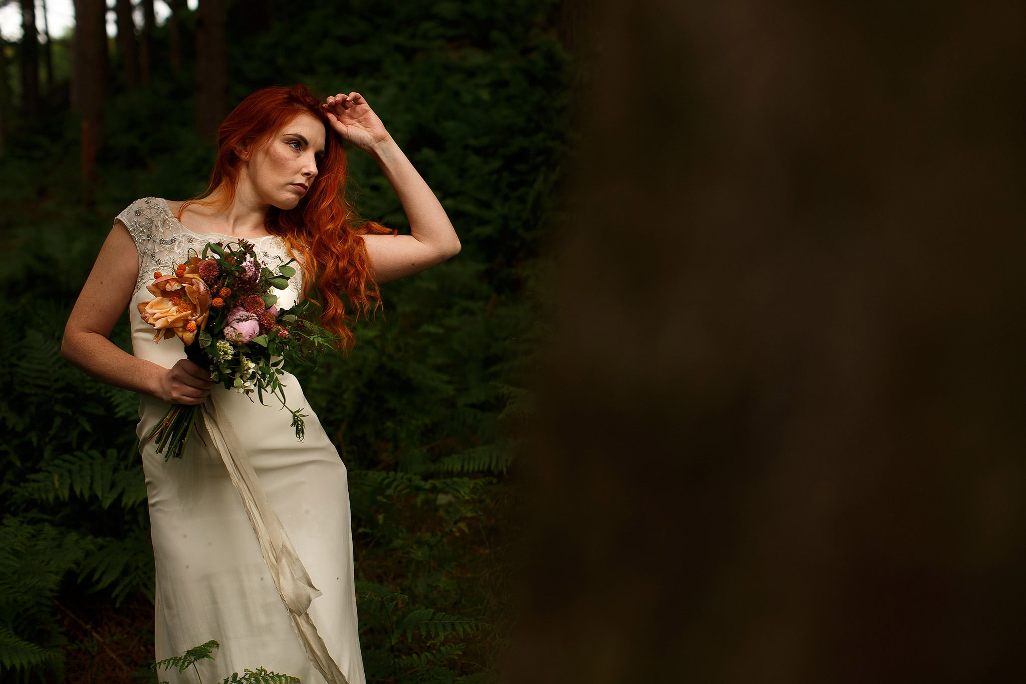 Red head bride wearing silk cream monsoon wedding dress in the woodland. Holding a DIY wedding bouquet.