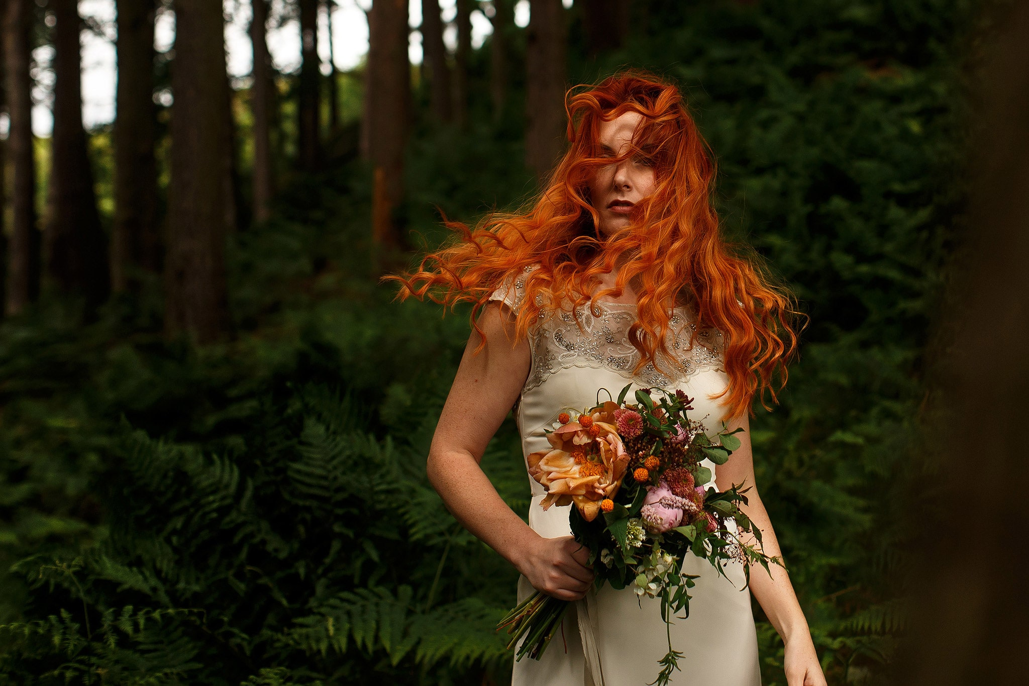 Curly red head bride shaking her long hair in the woodland during wedding photography workshop in Lancashire.