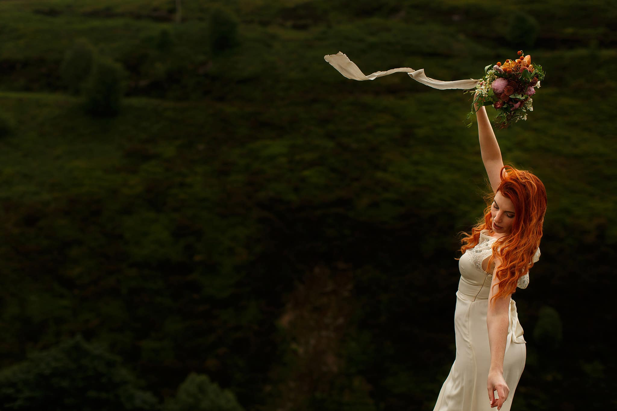 Red head bride balancing bare foot on a rock holding DIY wedding flower in the air as the ribbon and wedding dress blow in the wind.