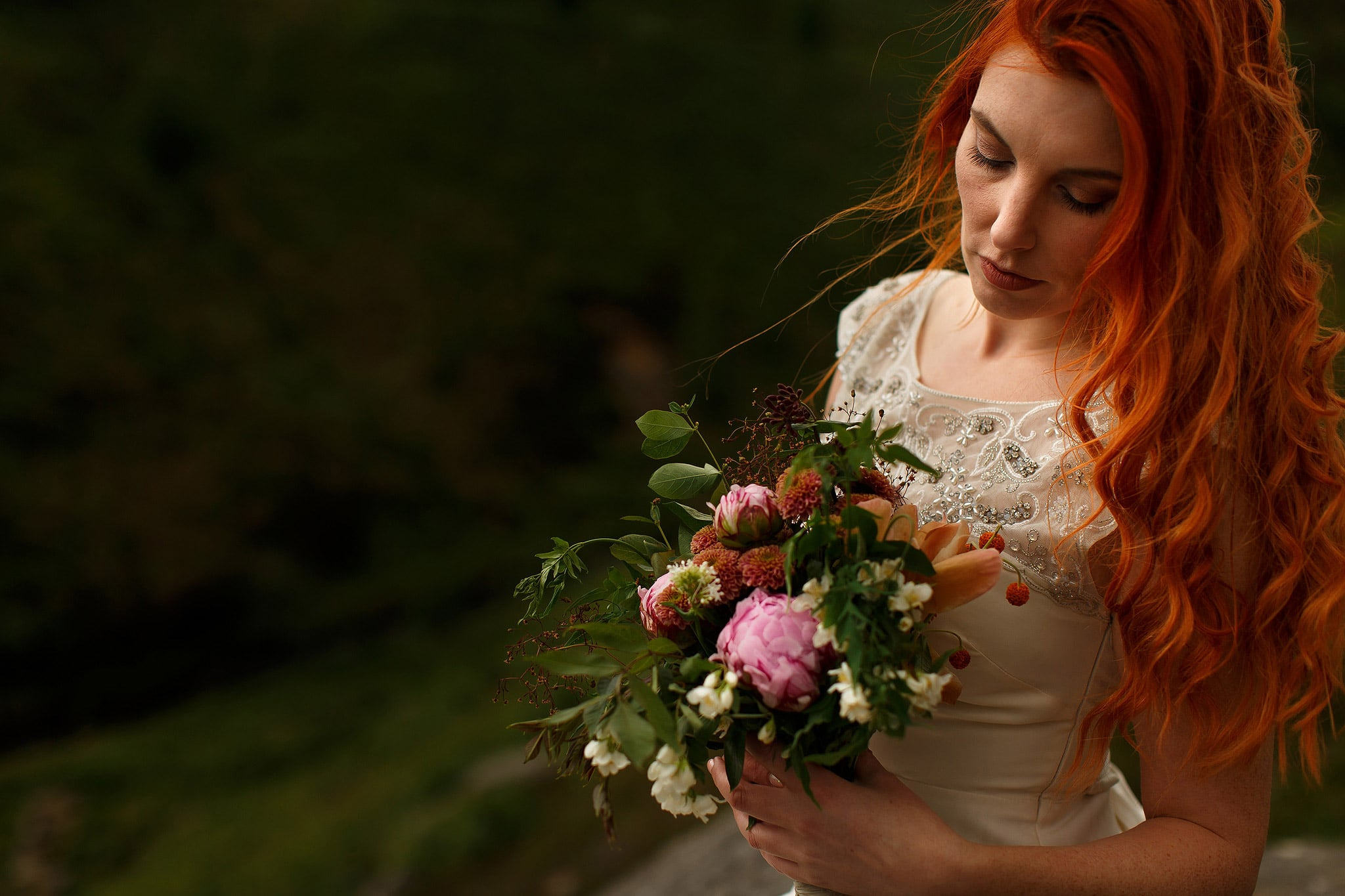Curly red head bride looking down into colourful DIY wedding bouquet as her hair blows in the wind.