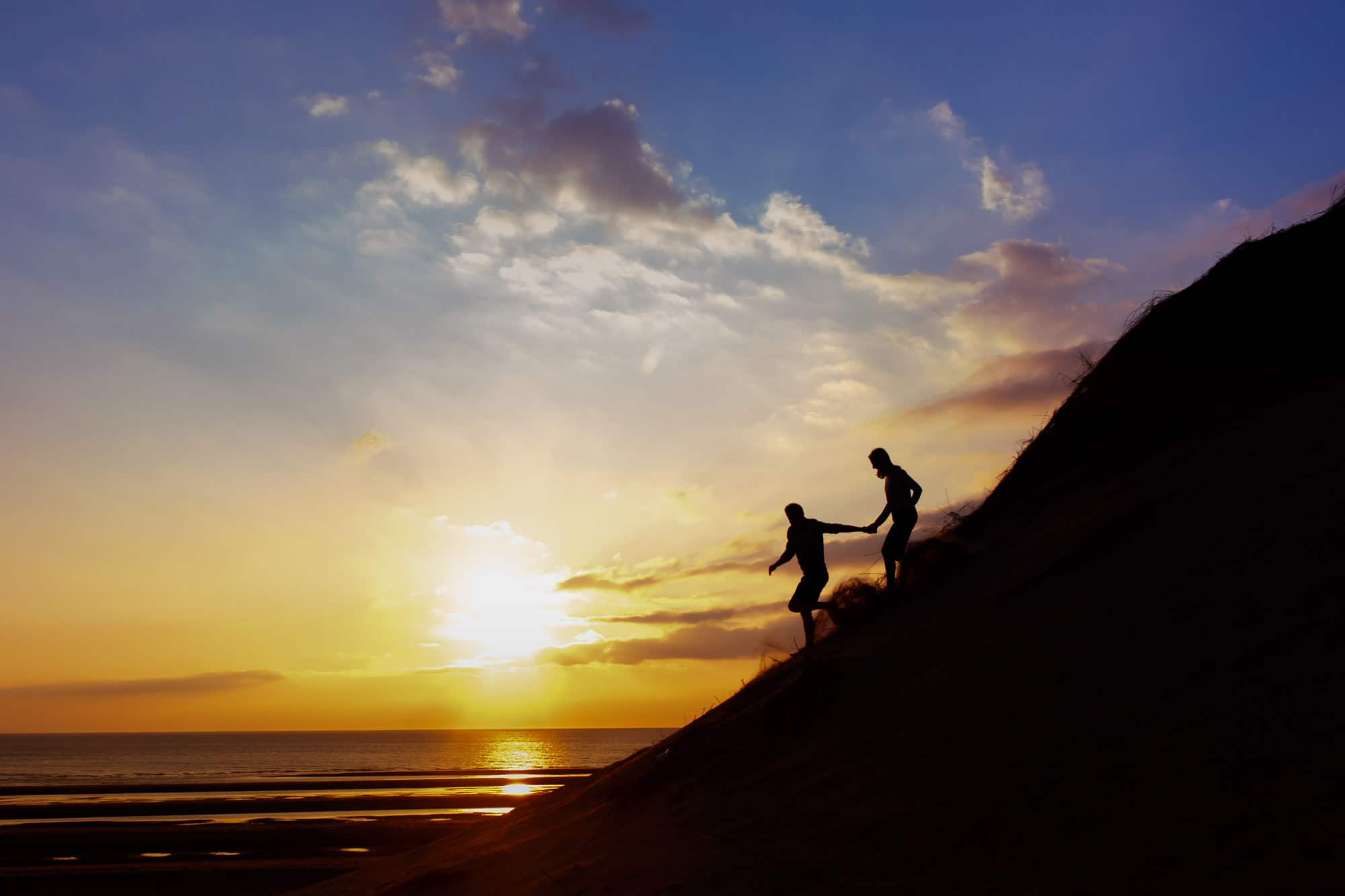 silhouette of couple running down the sand dunes at sunset on the beach