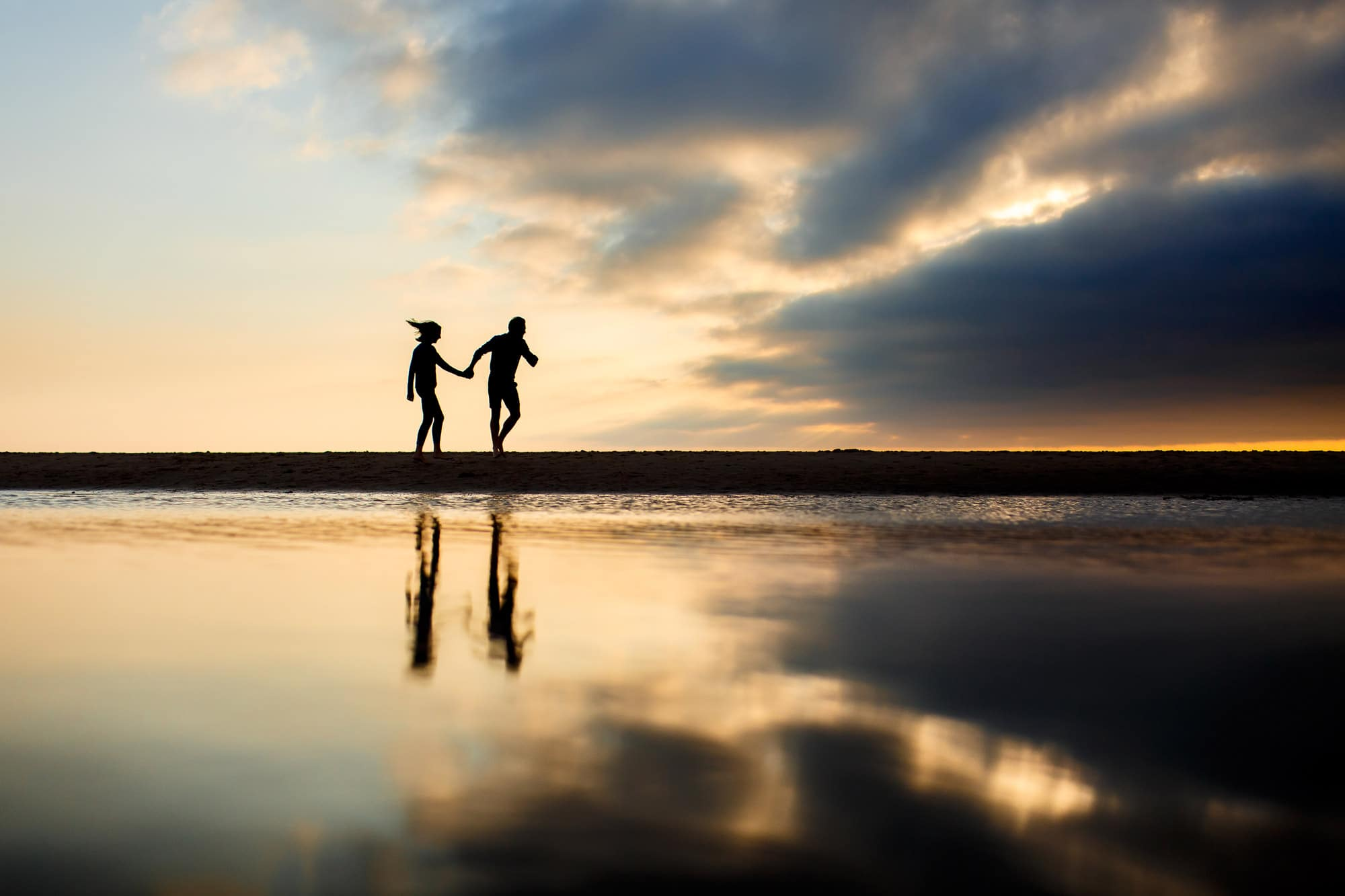 silhouette of couple running across the beach at sunset