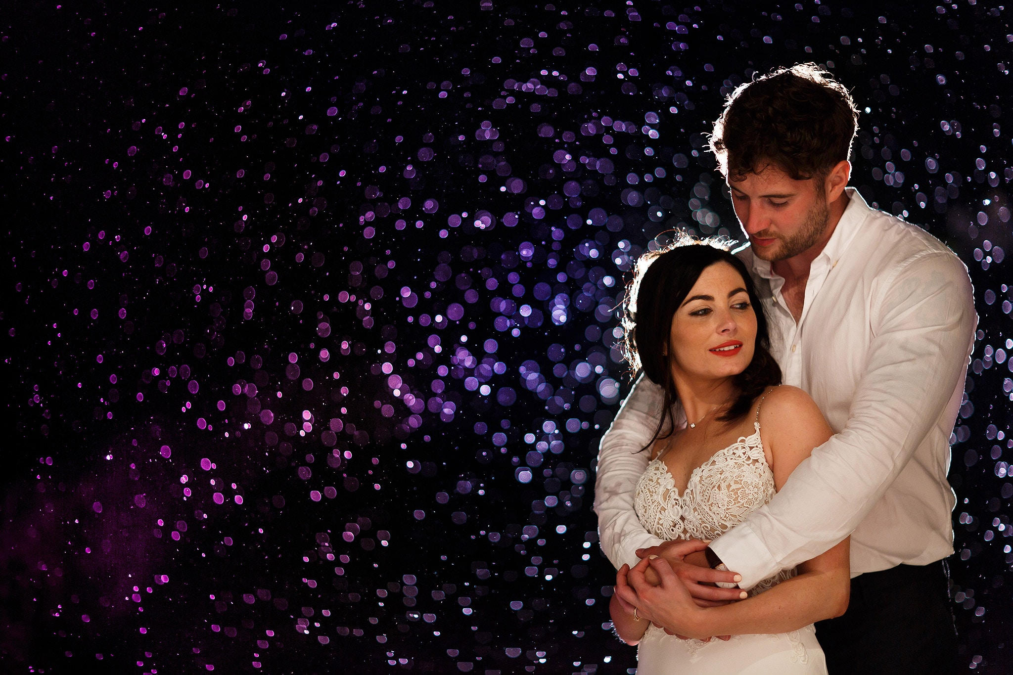 Magical wedding portrait of bride and groom taken in the rain. Lit with off camera flash the rain sparkles.