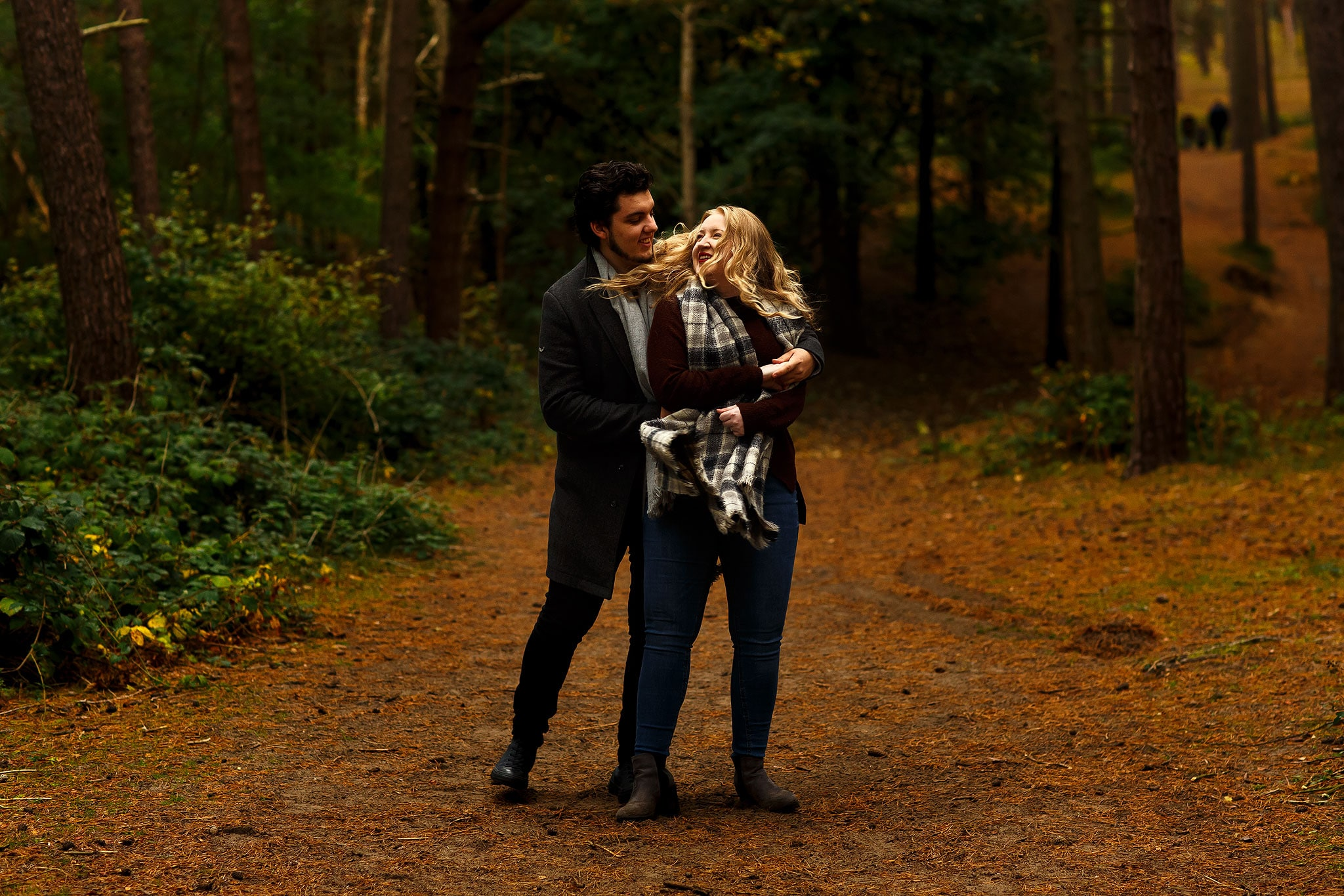 Autumn engagement shoot in the woods with golden leaves. Girl with flowing blonde hair.