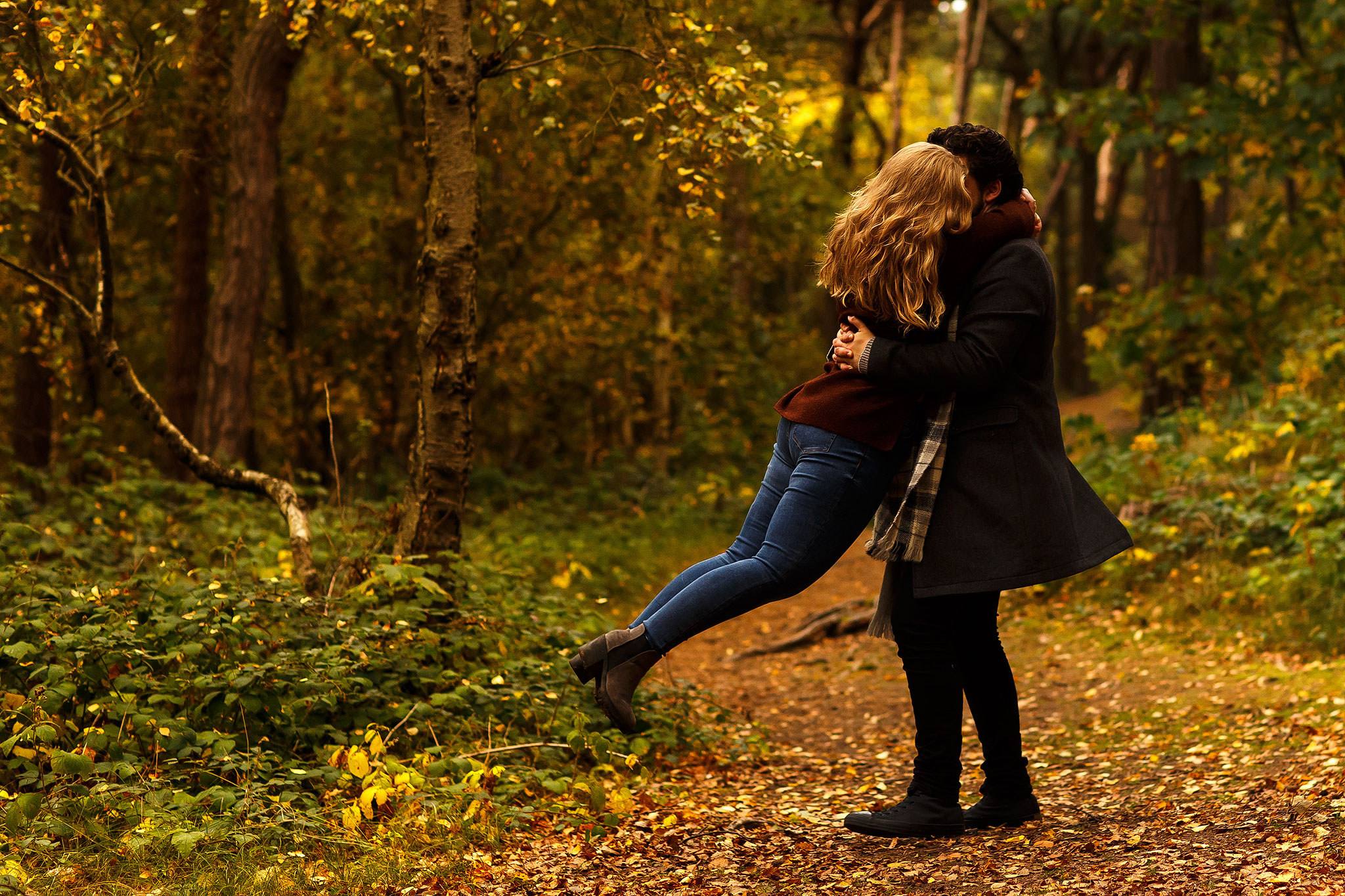 Autumn engagement shoot in the woods with golden leaves. Boy swinging girl around on the pathway.