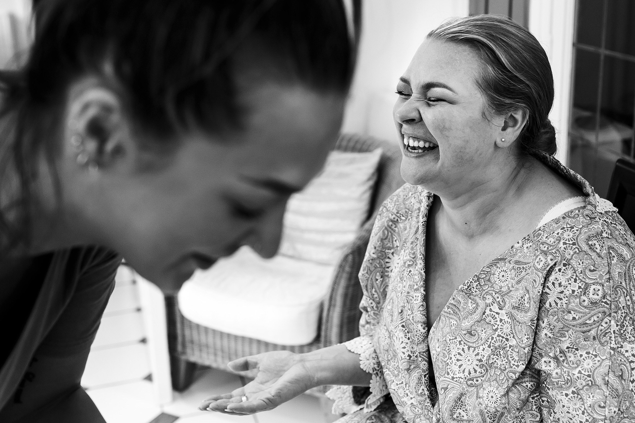 Black and white image of the bride laughing on the morning of her wedding whilst having make up applied