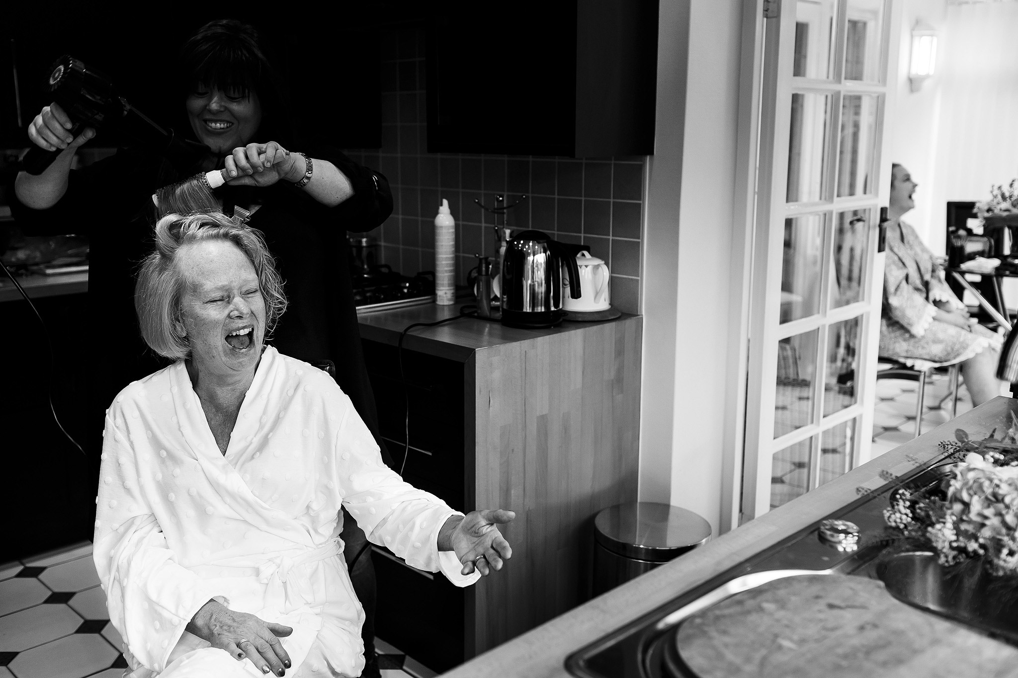 Black and white image of mother of the bride laughing on the morning of her wedding whilst having make up applied