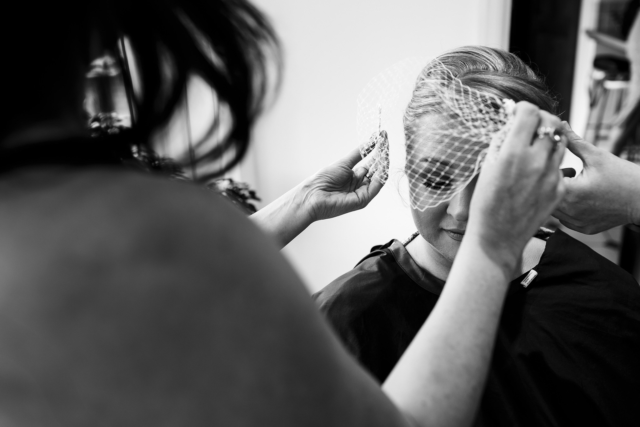 bride having birdcage veil fitted on wedding day