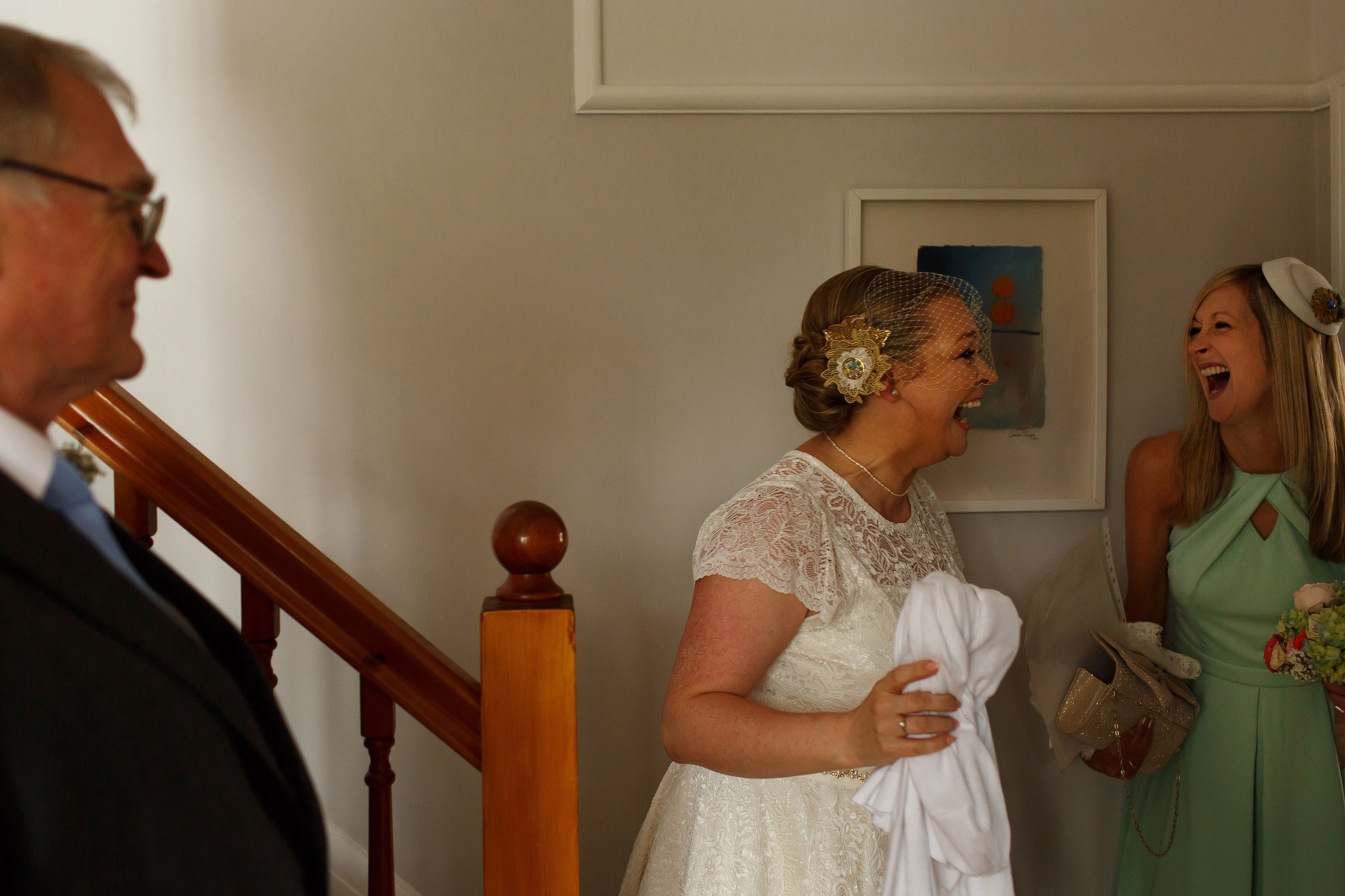 bride laughing with bridesmaids wearing birdcage veil