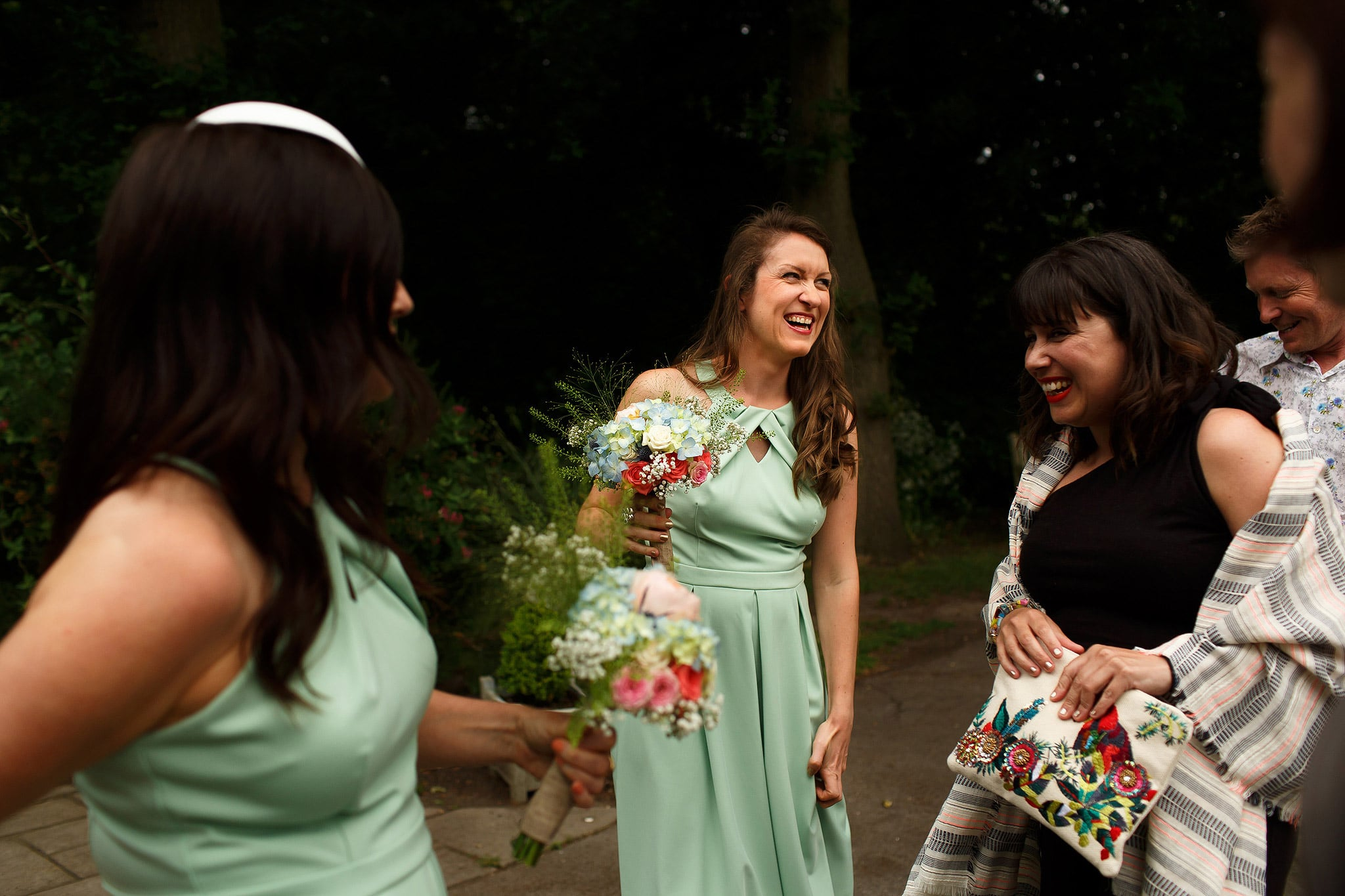 Bridesmaids wearing mint green dresses laughing