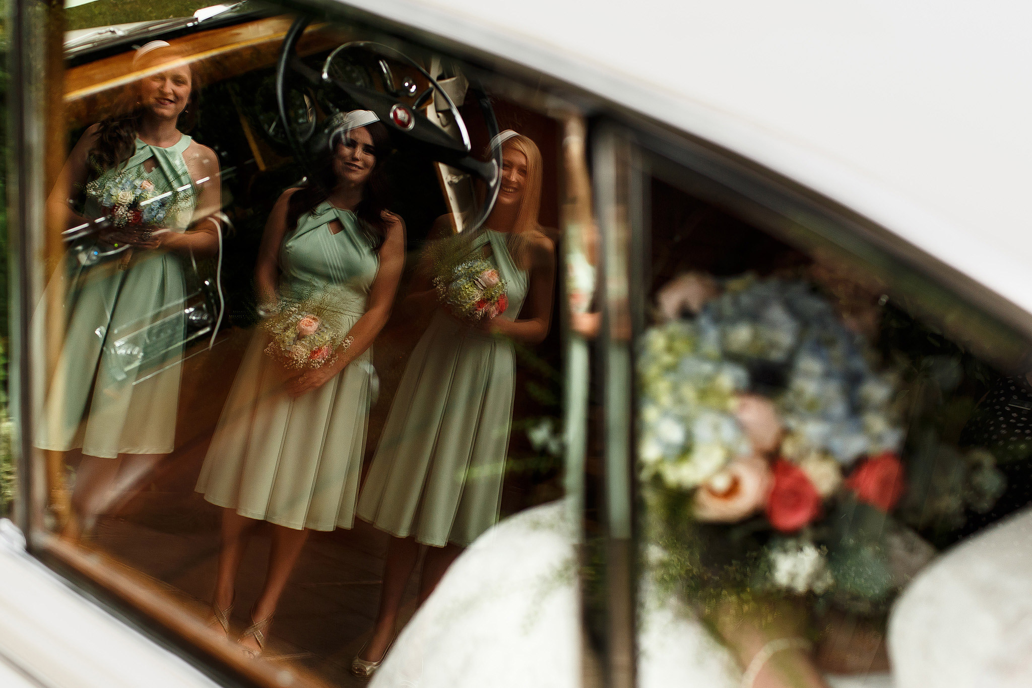 Bridesmaids wearing mint green knee length dresses holding multicoloured wild bouquets waiting for bride to step out of vintage wedding car