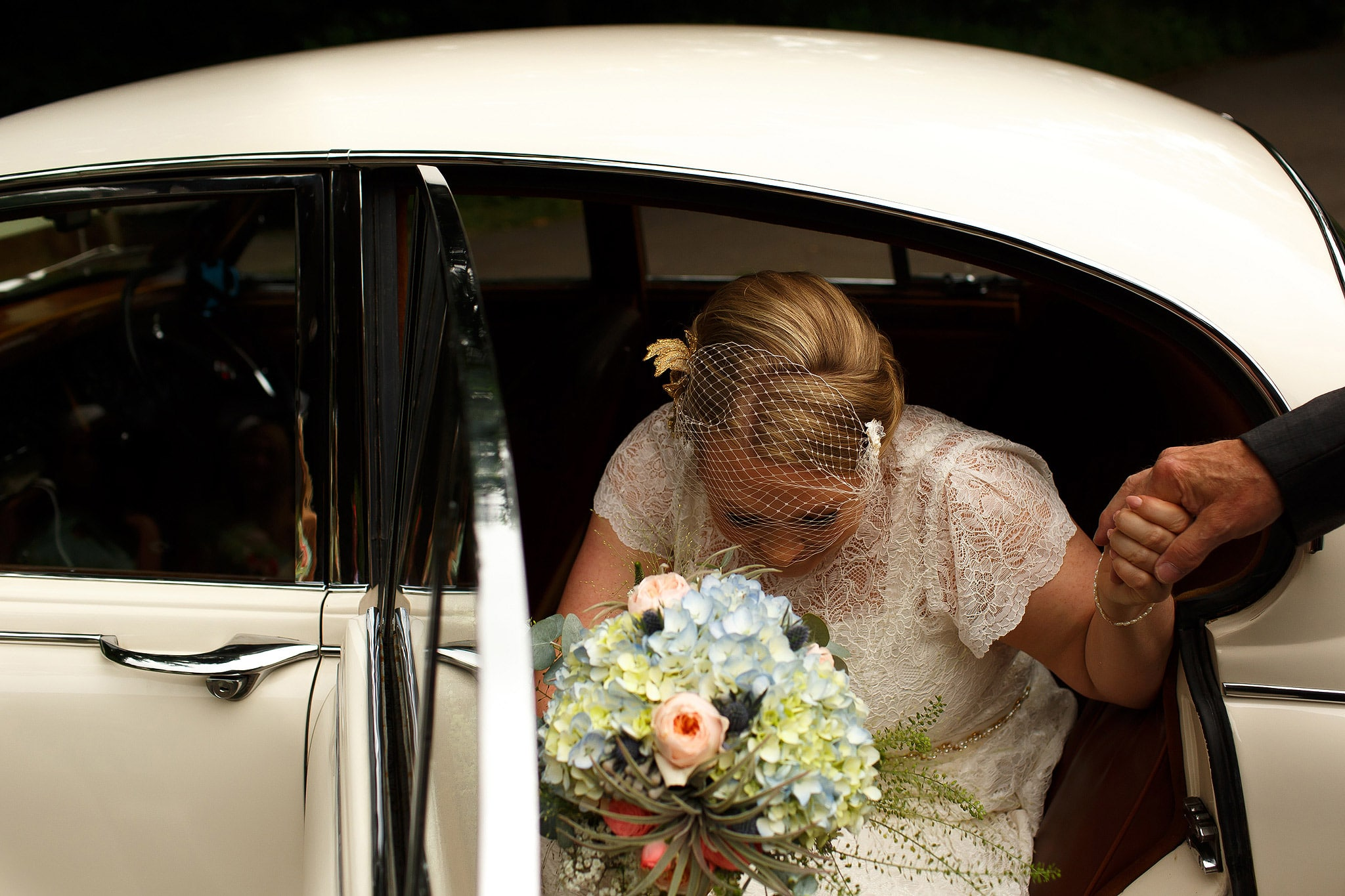 Bride wearing birdcage veil stepping out of vintage wedding car