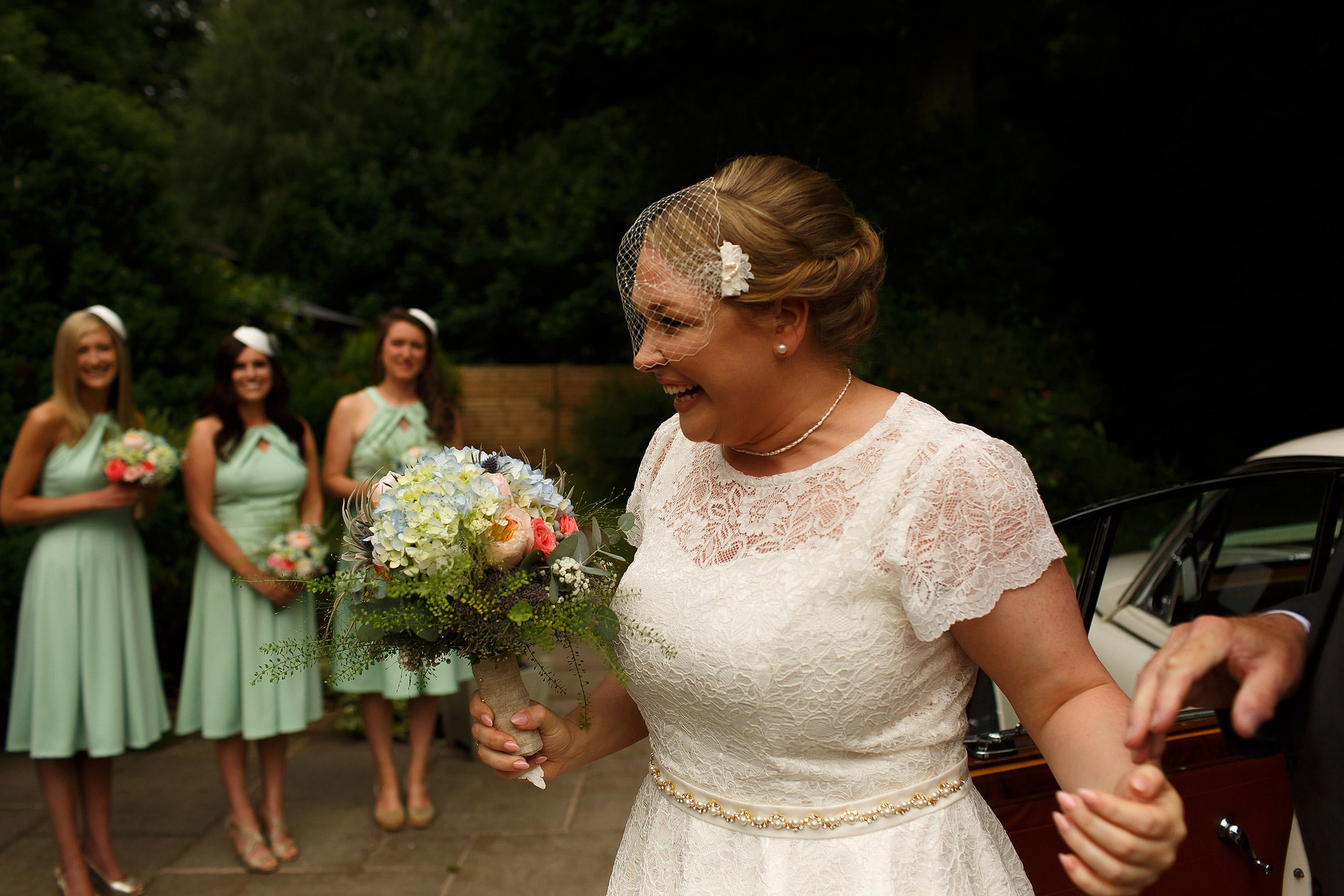 Bride wearing knee length tea dress with bridesmaids wearing mint green dresses