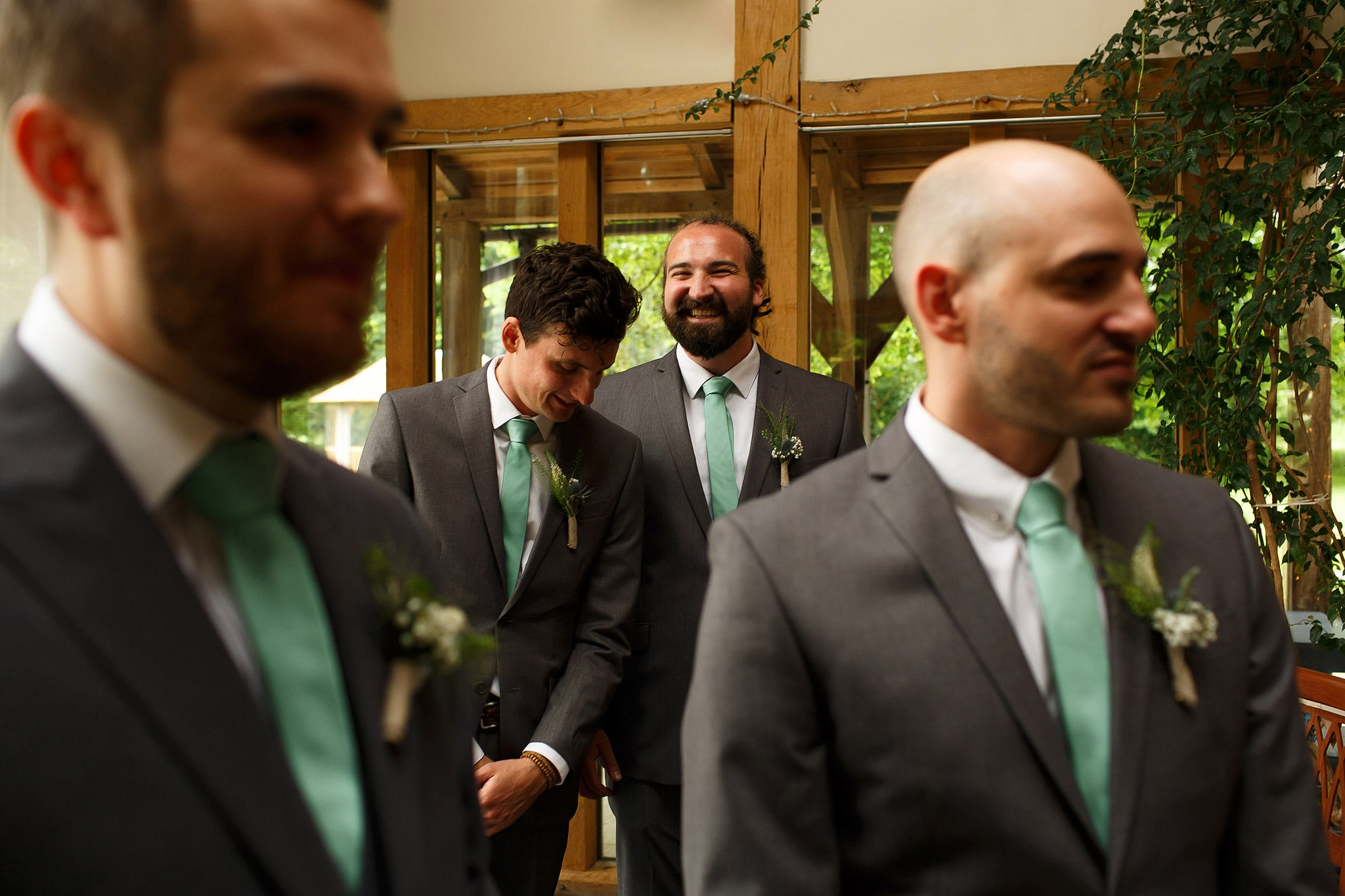 Groomsmen waiting at the top of the wedding aisle wearing grey suits and mint green ties