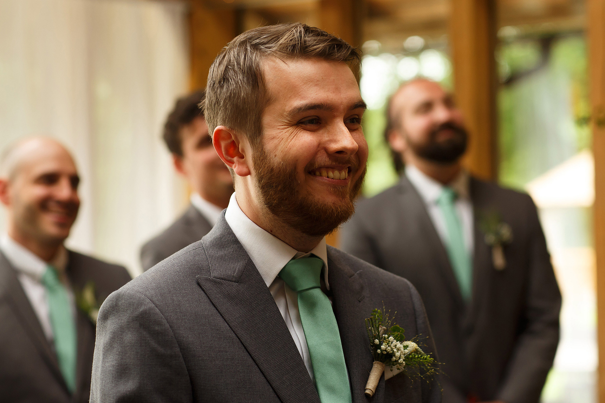 Groom wearing grey suit and mint green tie smiling as he sees bride for the first time