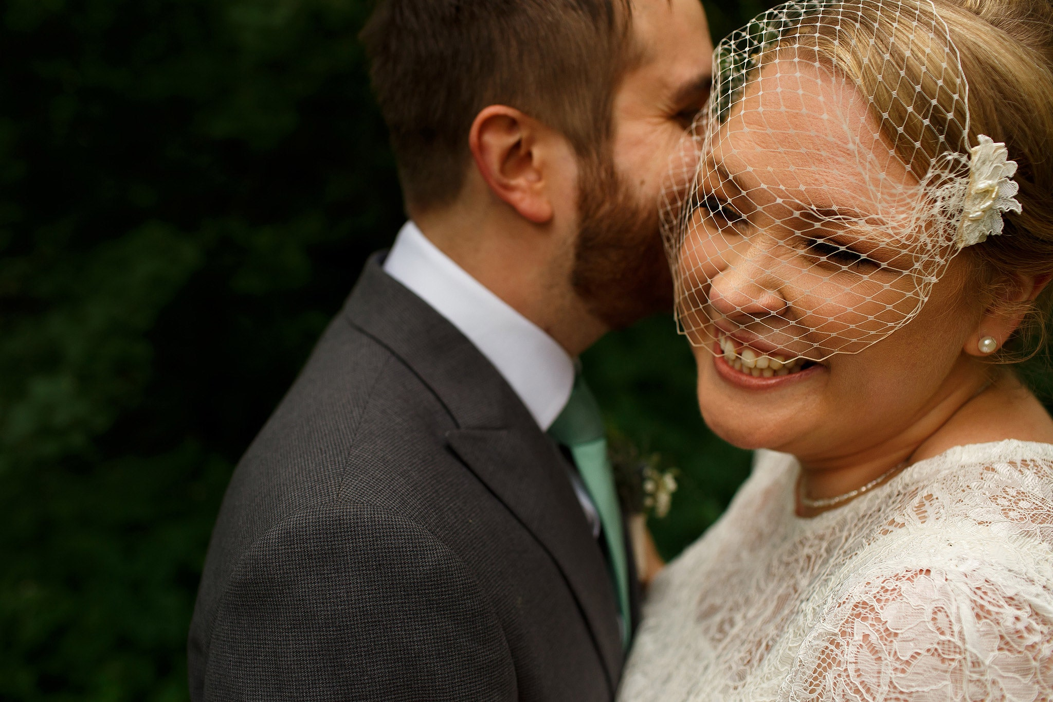 Close up portrait of bride wearing birdcage veil and groom during portraits in the countryside at the Oak Tree at Peover wedding
