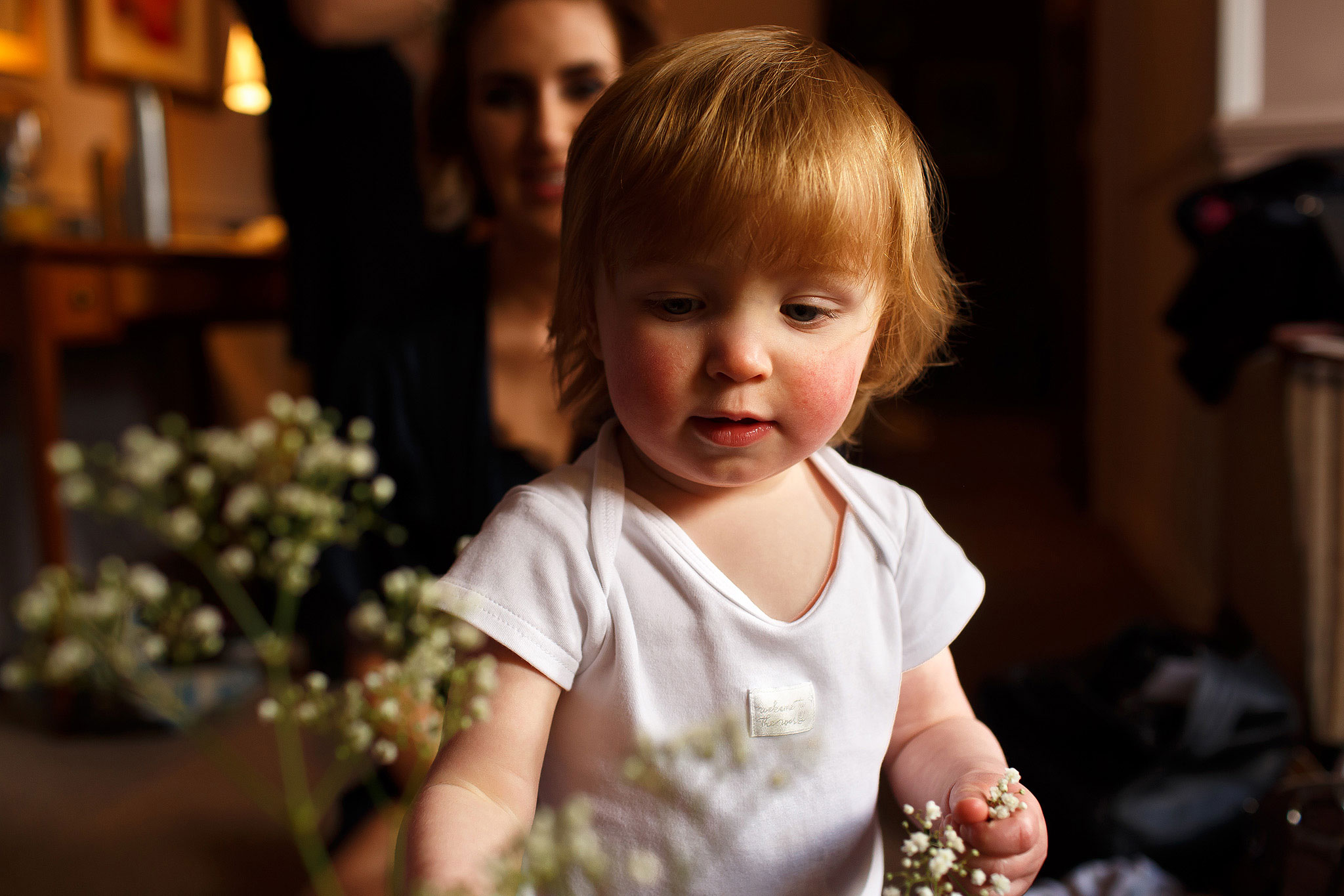 Flower girl with blonde hair looking at wedding flowers
