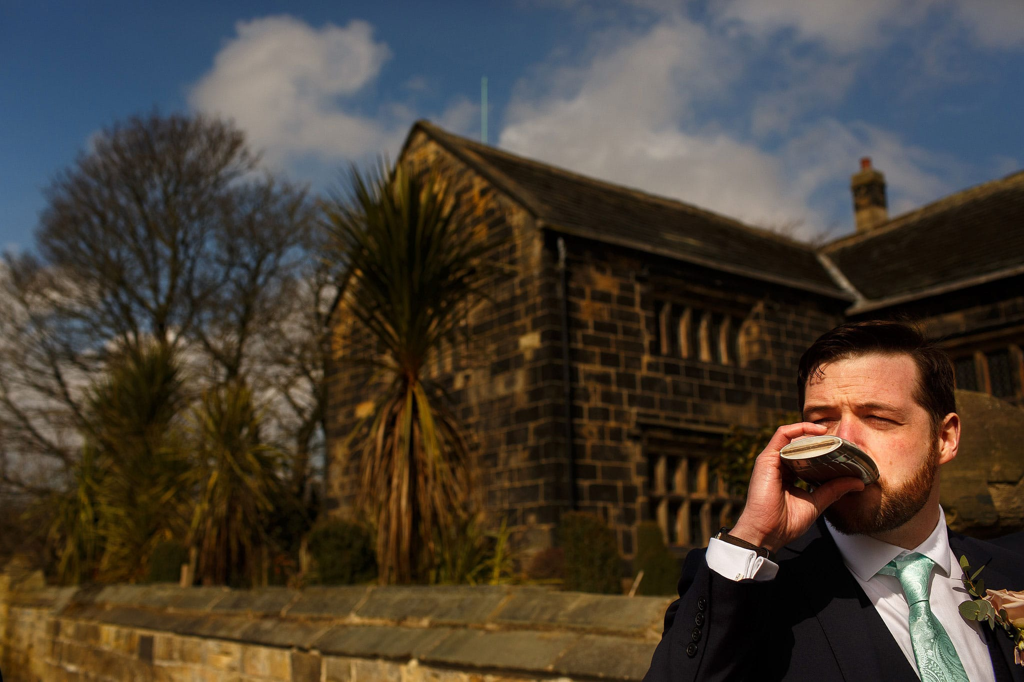 Groom drinking from hip flask outside Oakwell Hall