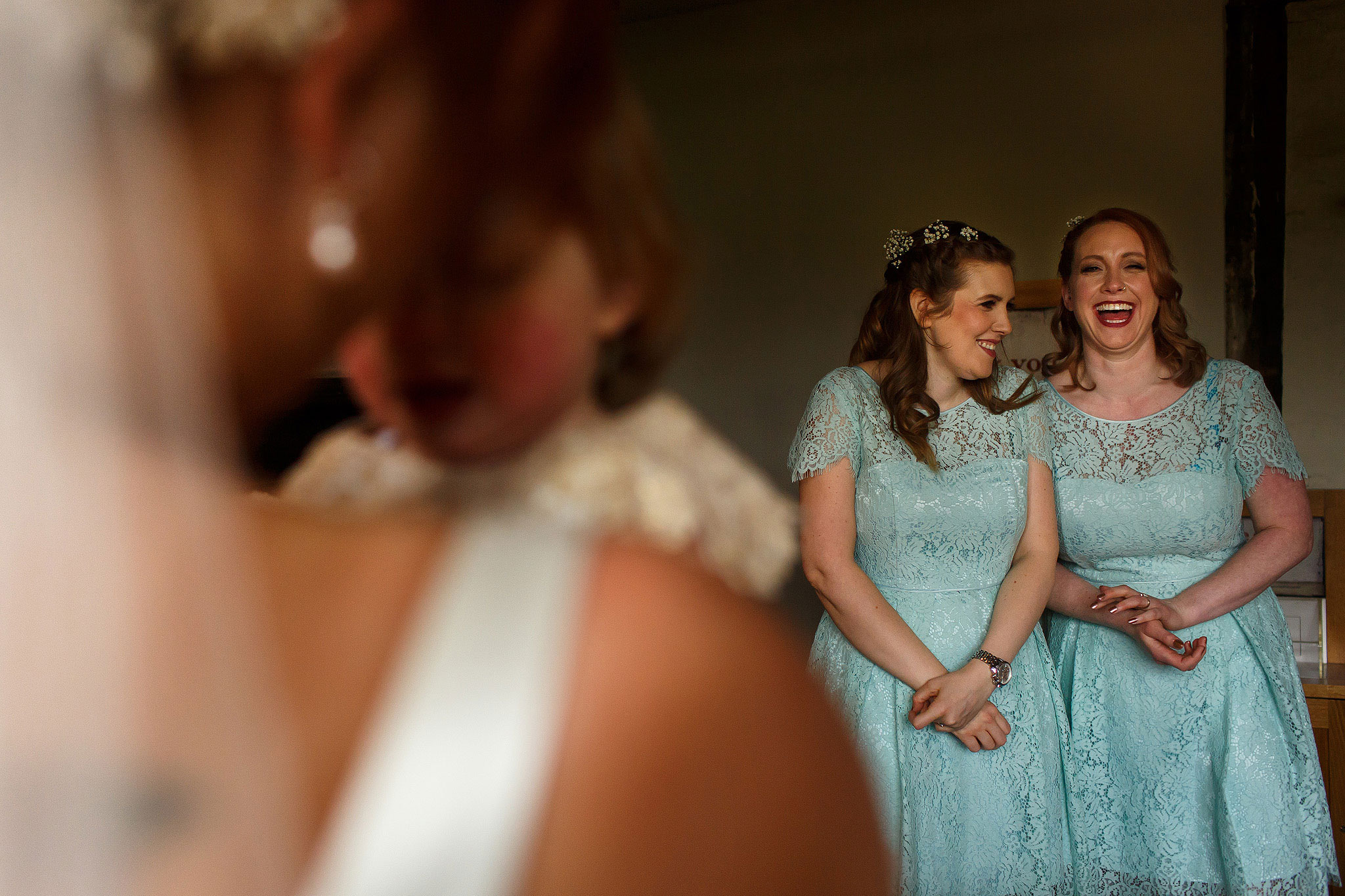 Bridemaids giggling wearing pale blue dresses before Oakwell Hall wedding ceremony