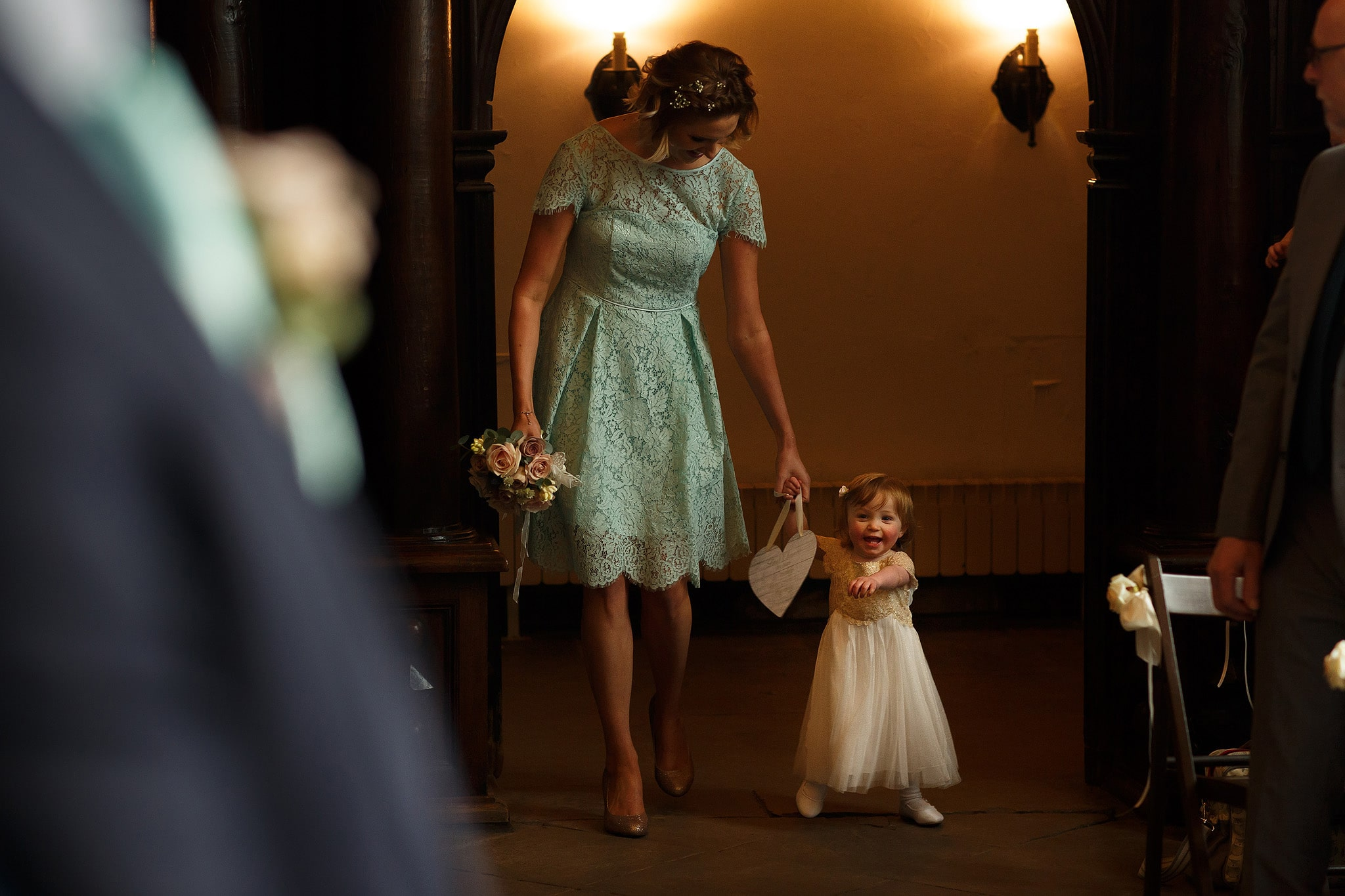 Bridemaid walking the flower girl down the aisle before Oakwell Hall wedding ceremony