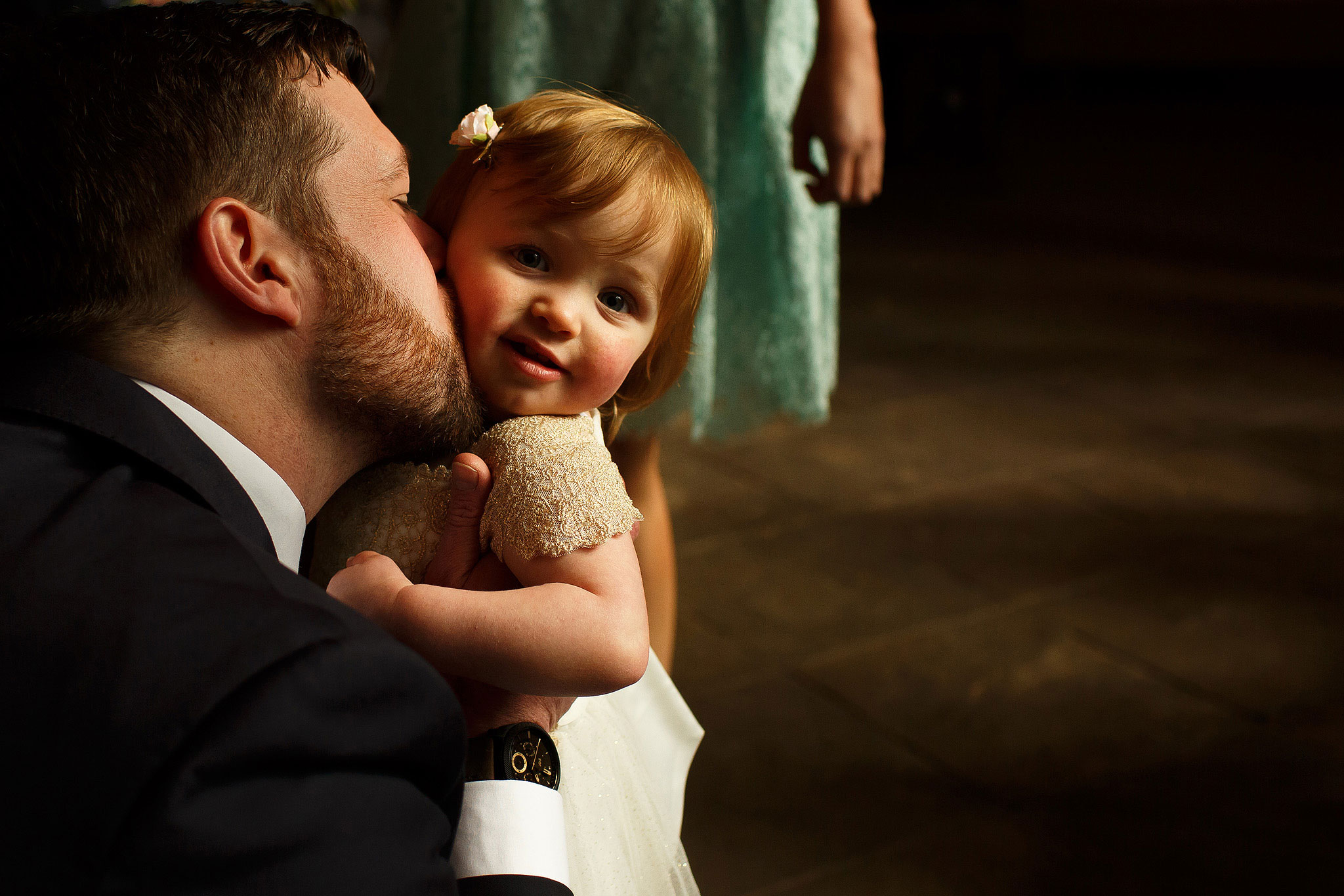 Groom giving flower girl a kiss before Oakwell Hall wedding ceremony