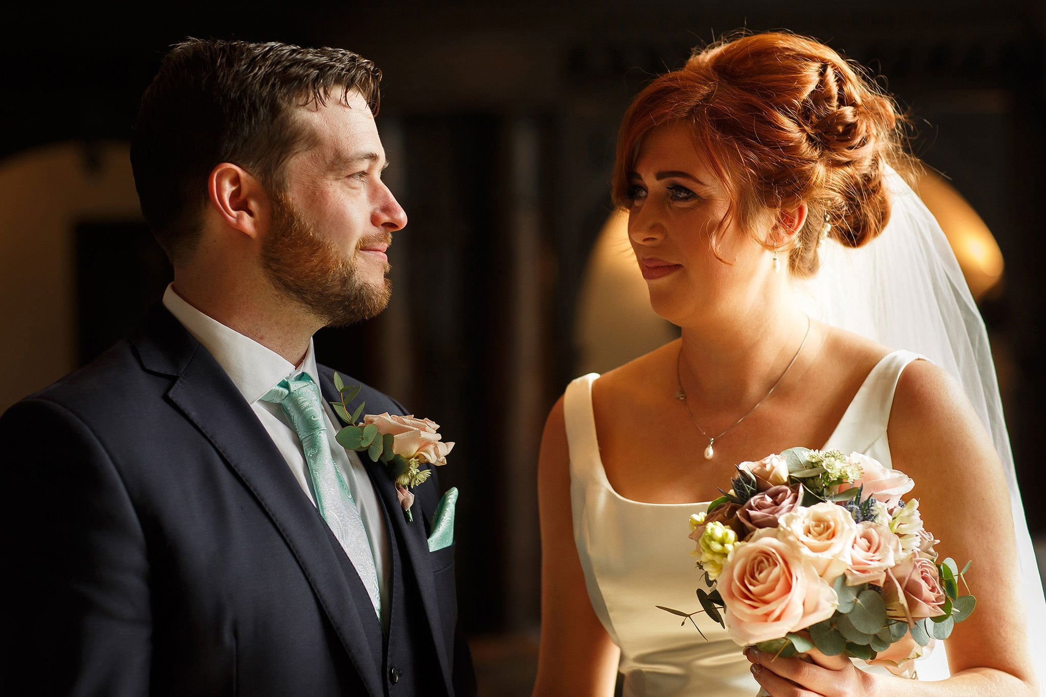 Bride and groom looking into each others eyes during wedding ceremony at Oakwell Hall Country Park