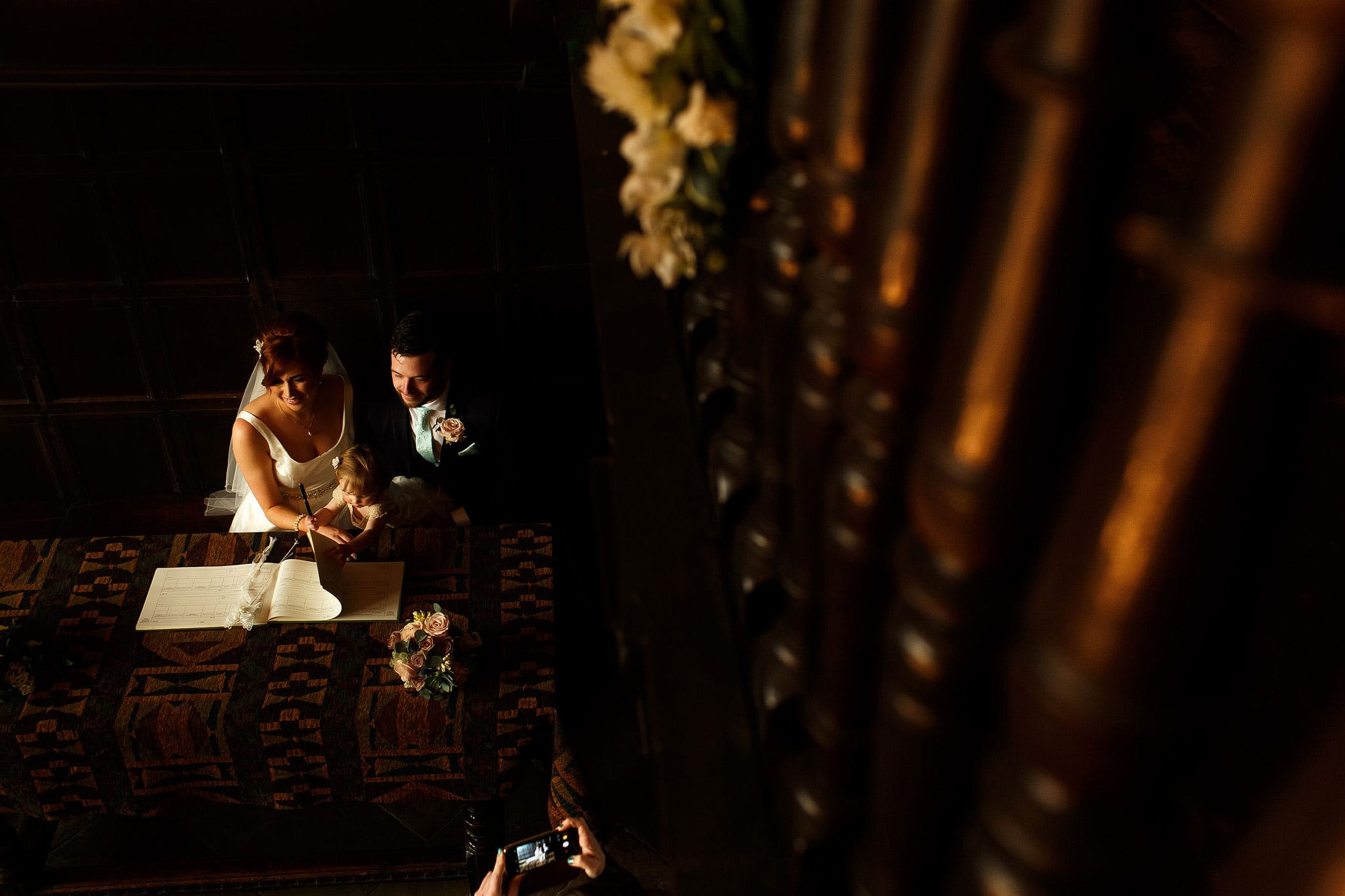 Bride and groom signing the register taken from the balcony inside the Great Hall at Oakwell Hall