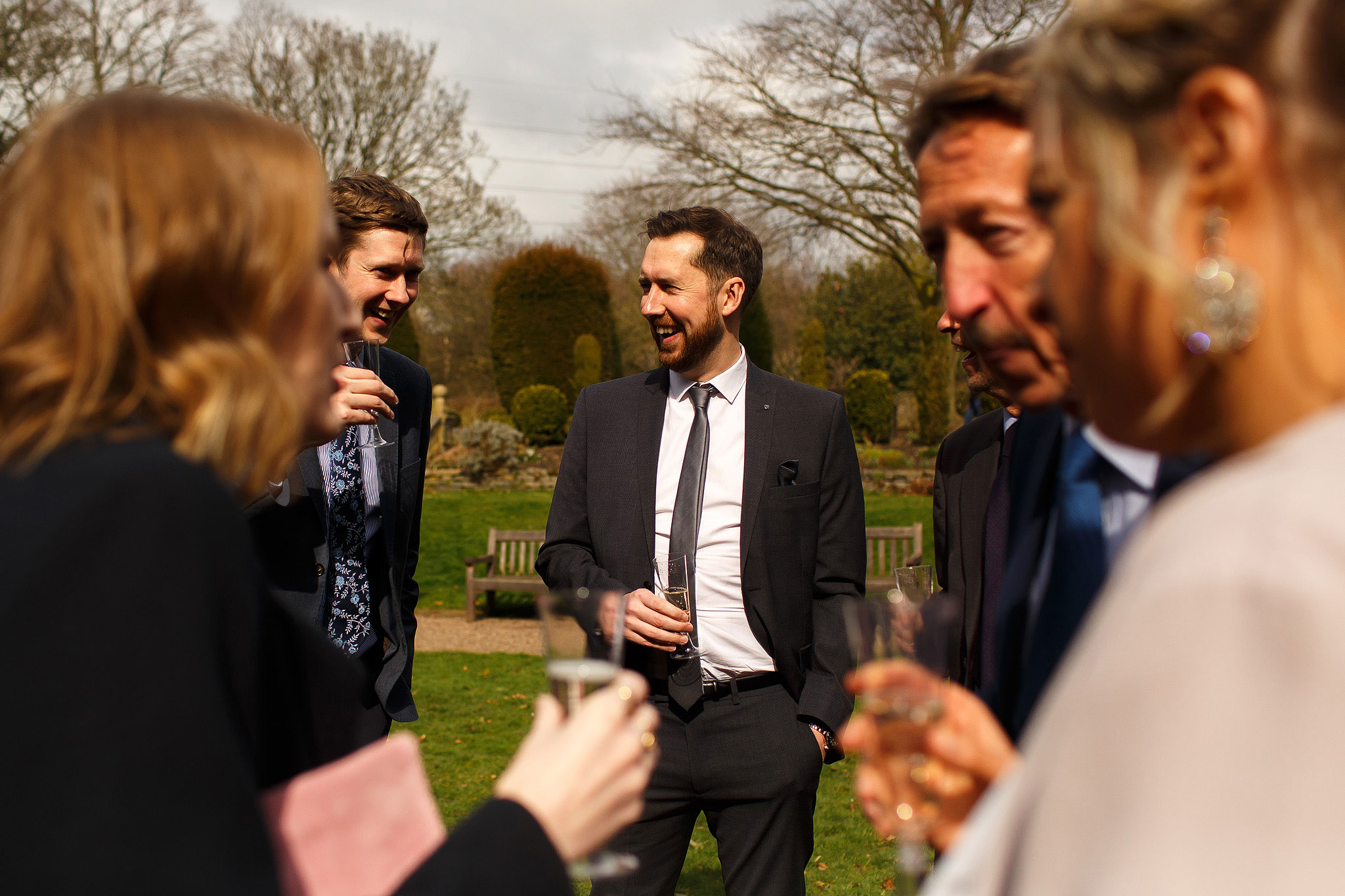 Guests laughing during the drinks reception in the walled garden at Oakwell Hall