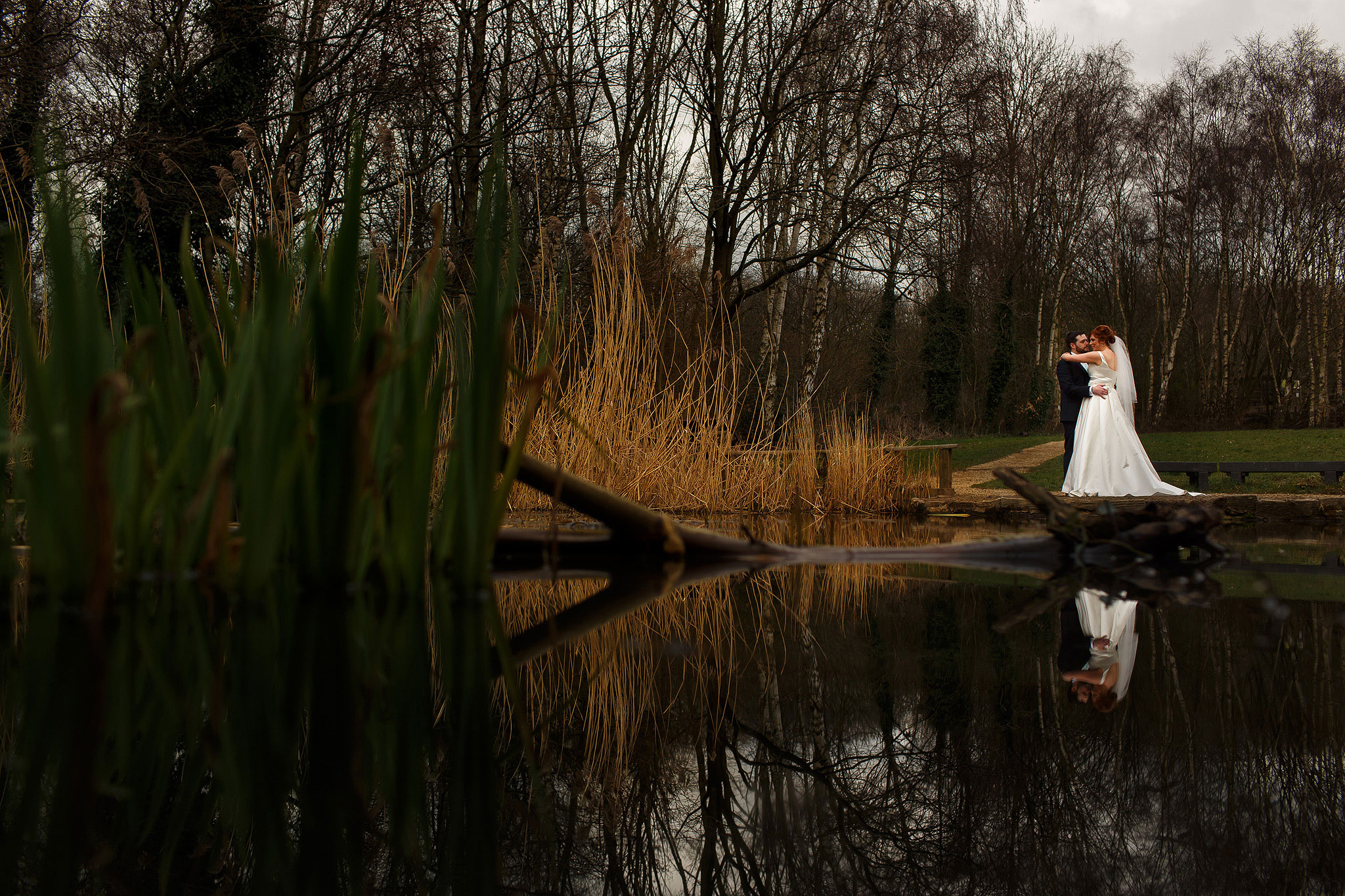 Bride and groom wedding portrait taken from across the lake in the countryside at Oakwell Hall Country Park wedding