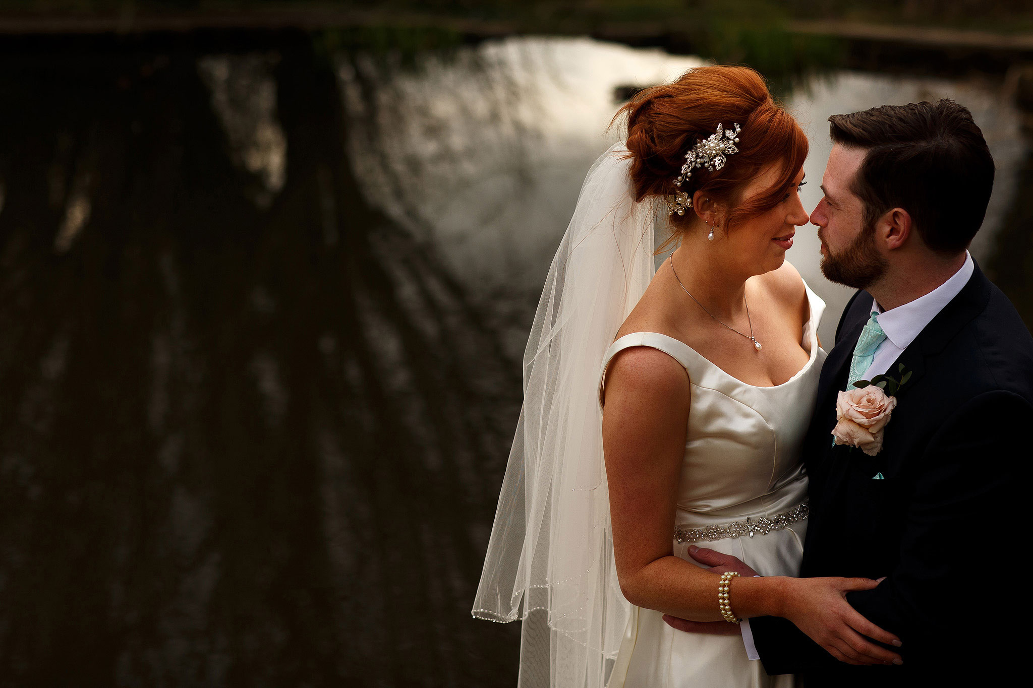Bride with red hair and crystal headpiece and long veil facing the groom during wedding portraits at Oakwell Hall