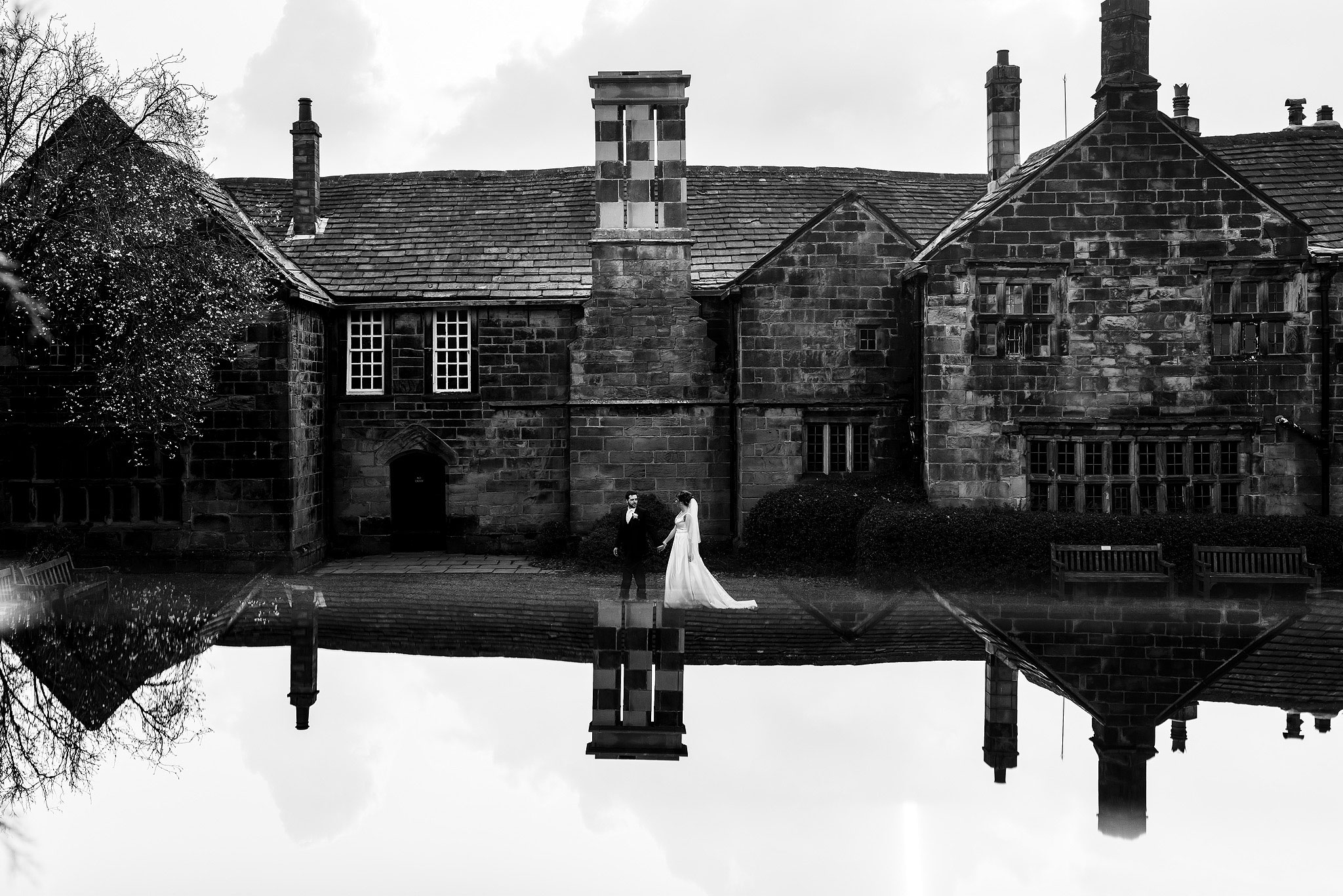 Bride and groom walking across the front of Oakwell Hall Country Park with reflection of sky
