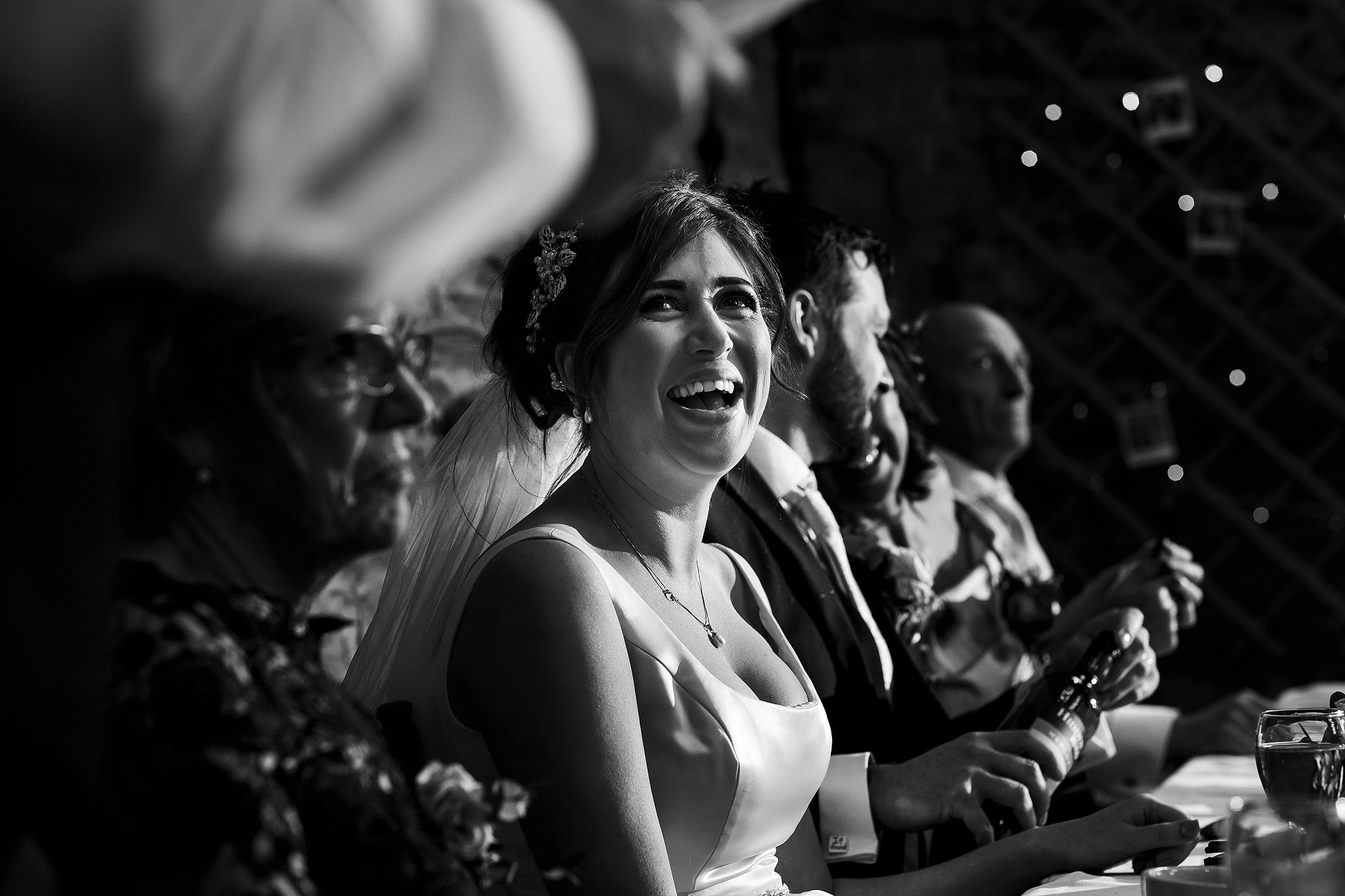 Bride laughing during wedding speeches inside the Barn at Oakwell Hall wedding reception