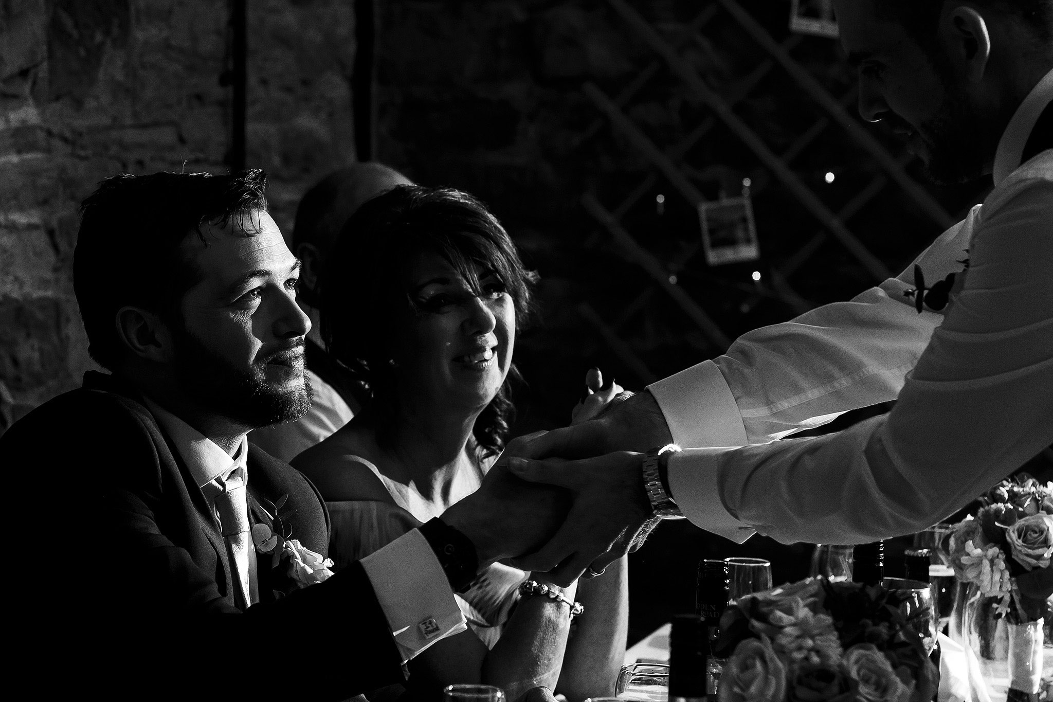 Groom laughing during wedding speeches inside the Barn at Oakwell Hall wedding reception