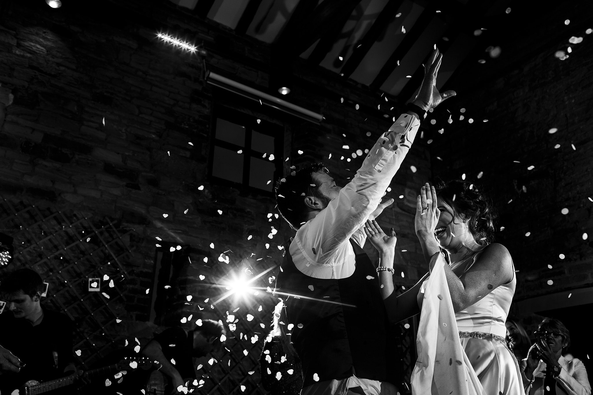 Bride and groom's first dance with confetti canons during Oakwell Hall Barn wedding reception