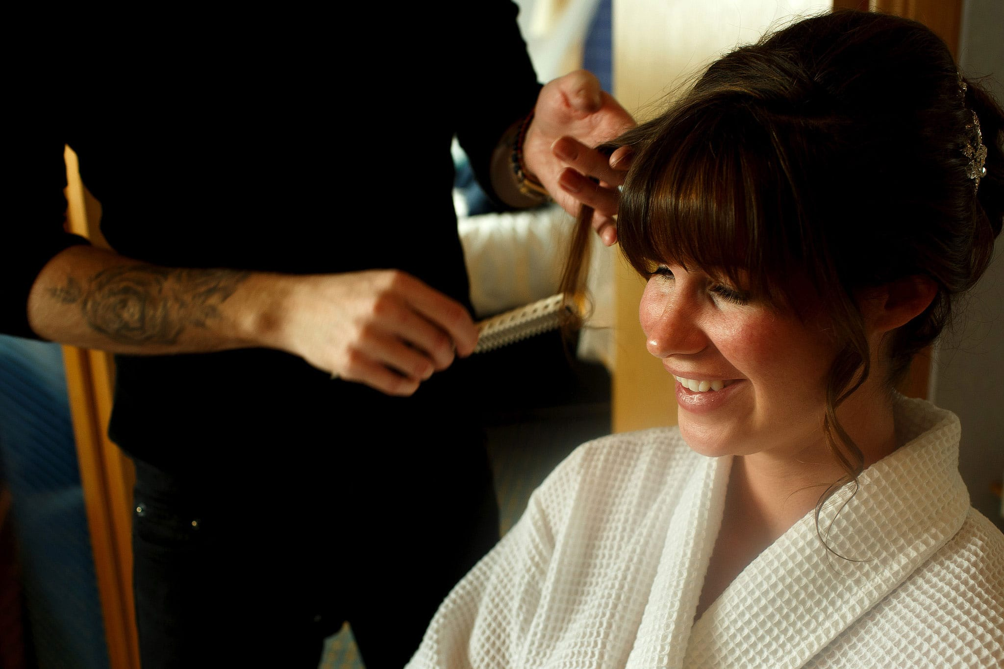Brunette bride with full fringe having hair piece applied during bridal preparations