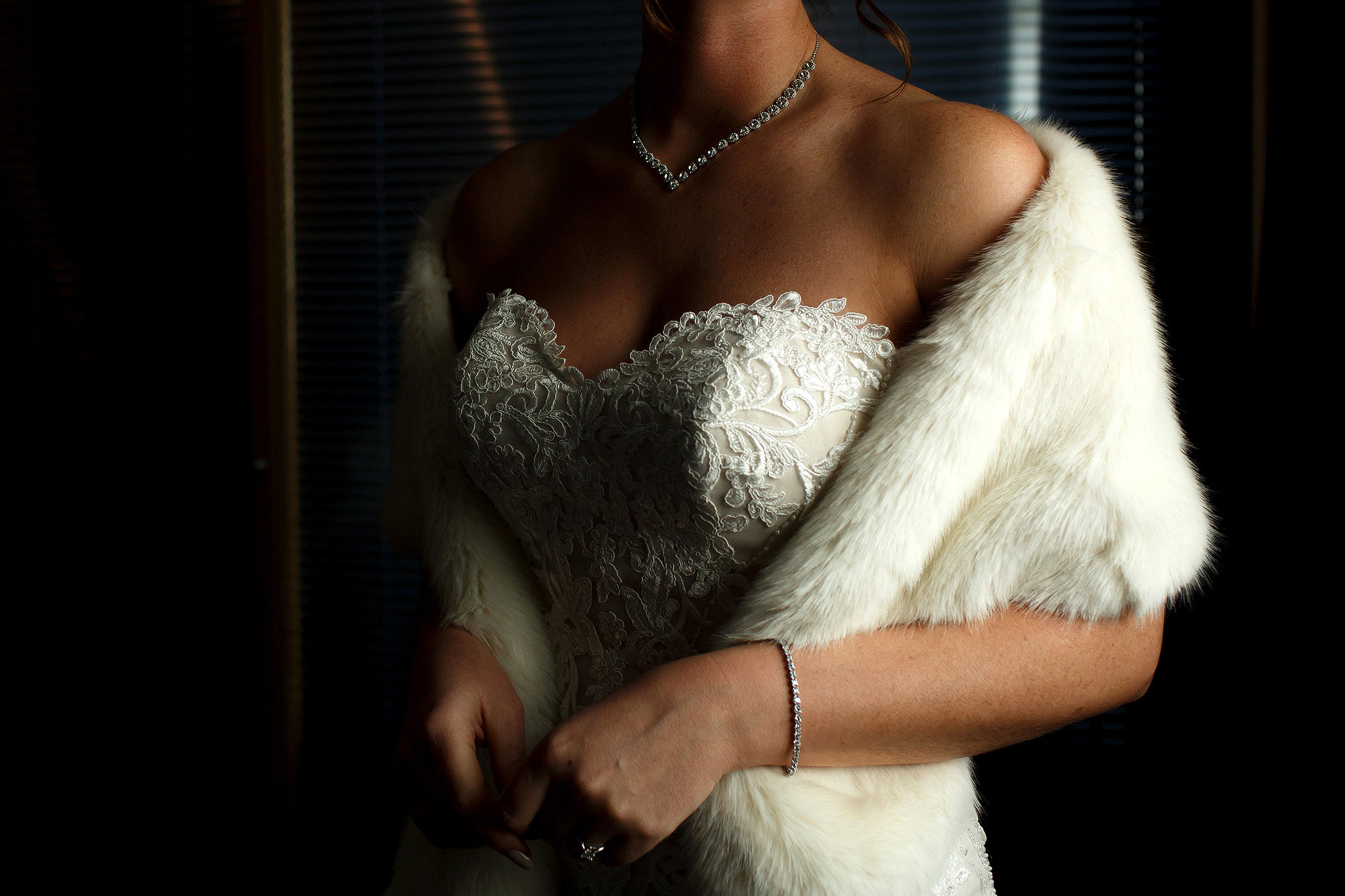 Bride wearing lace strapless dress with fur shrug on winter wedding day at Rivington Hall Barn