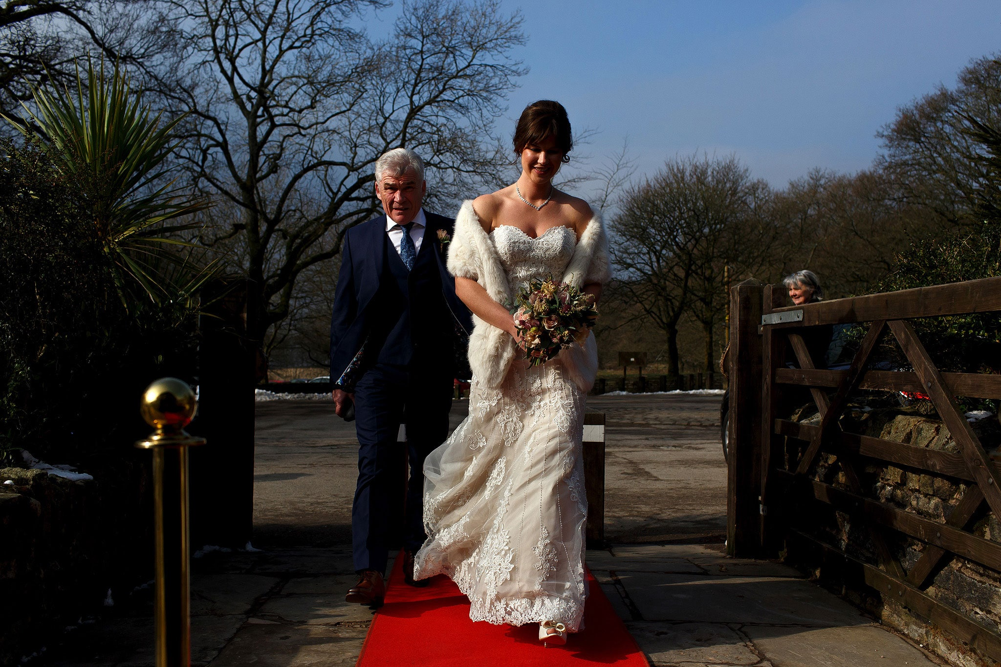 Bride and her father making their entrance into Rivington Hall Barn in winter down the red carpet