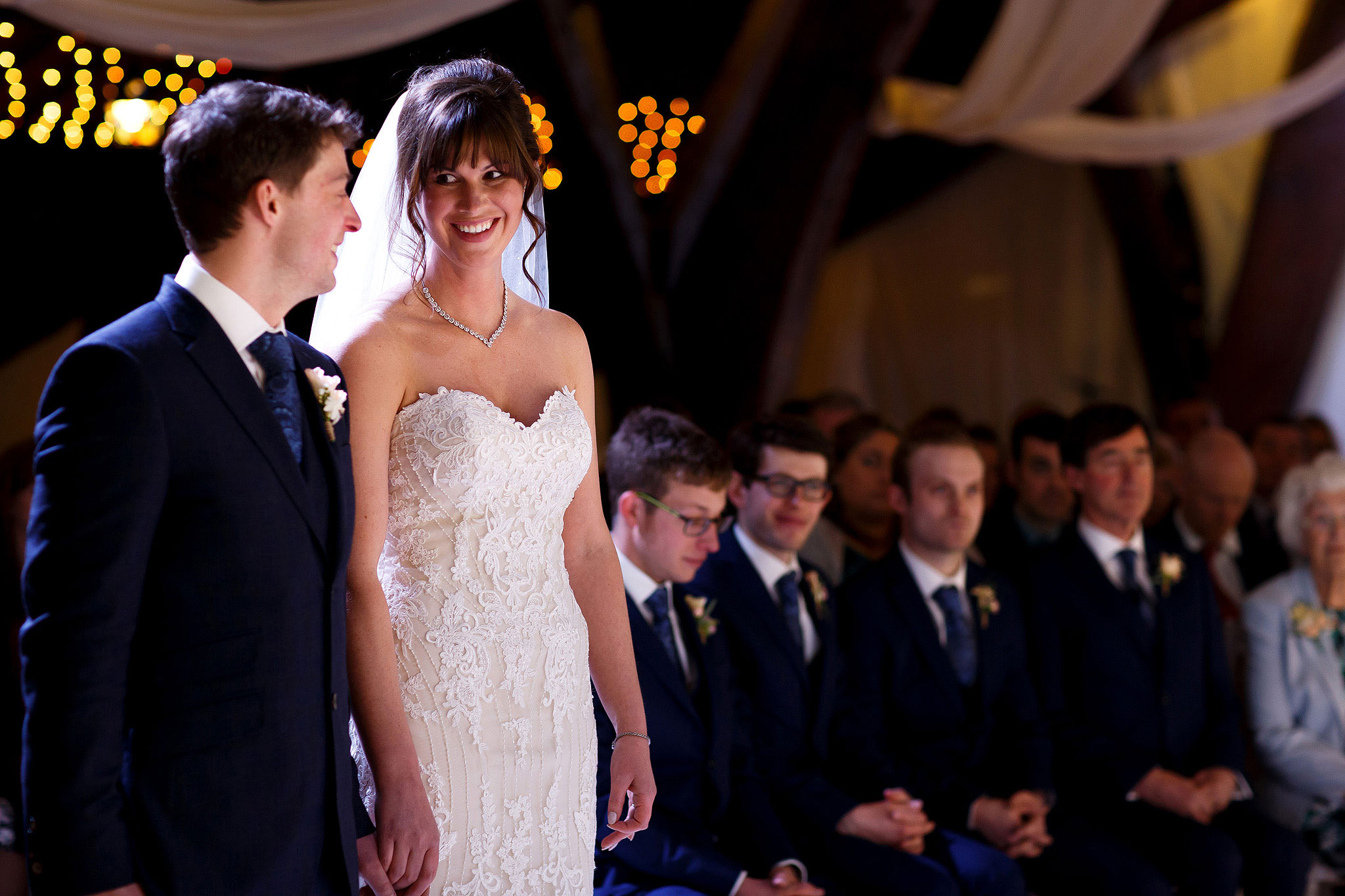 Bride wearing strapless lace wedding dress smiling towards her groom at the top of the aisle during Rivington Hall Barn civil ceremony