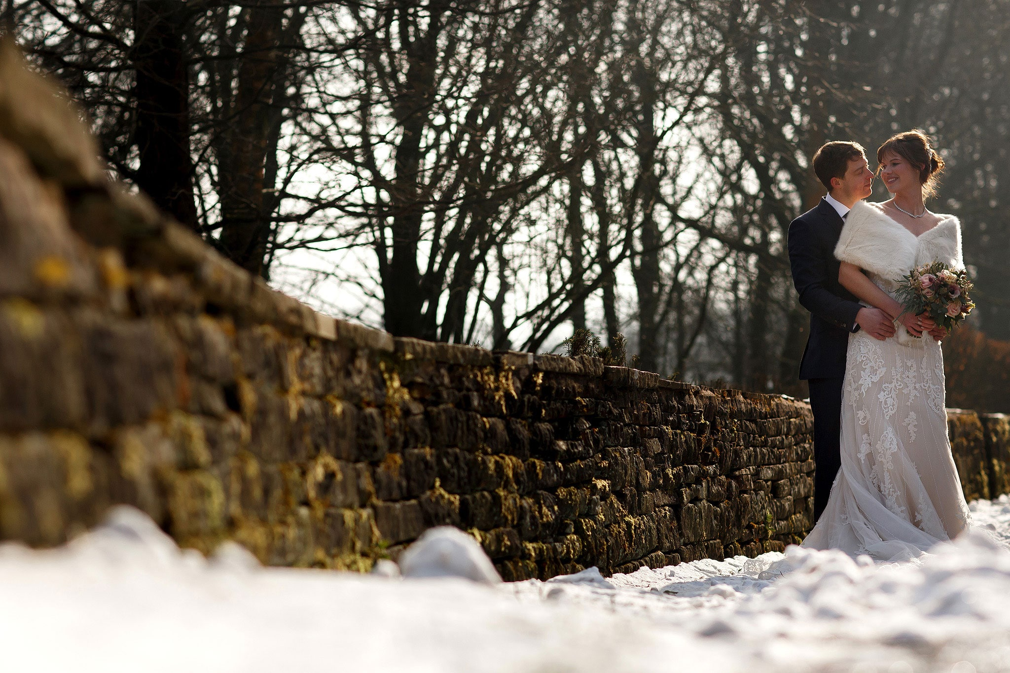 Bride wearing strapless lace wedding dress and fur shrug walking down the drive at Rivington Hall Barn on a snowy wedding day in February