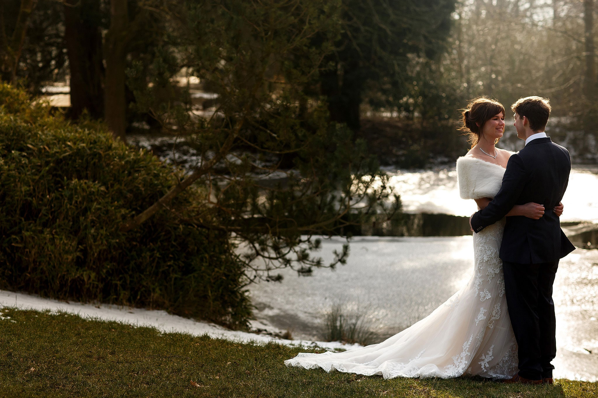 Wedding portrait of bride wearing strapless lace wedding dress and fur shrug in the arms of her husband on a cold winters wedding day with the lake in the background at Rivington Hall Barn