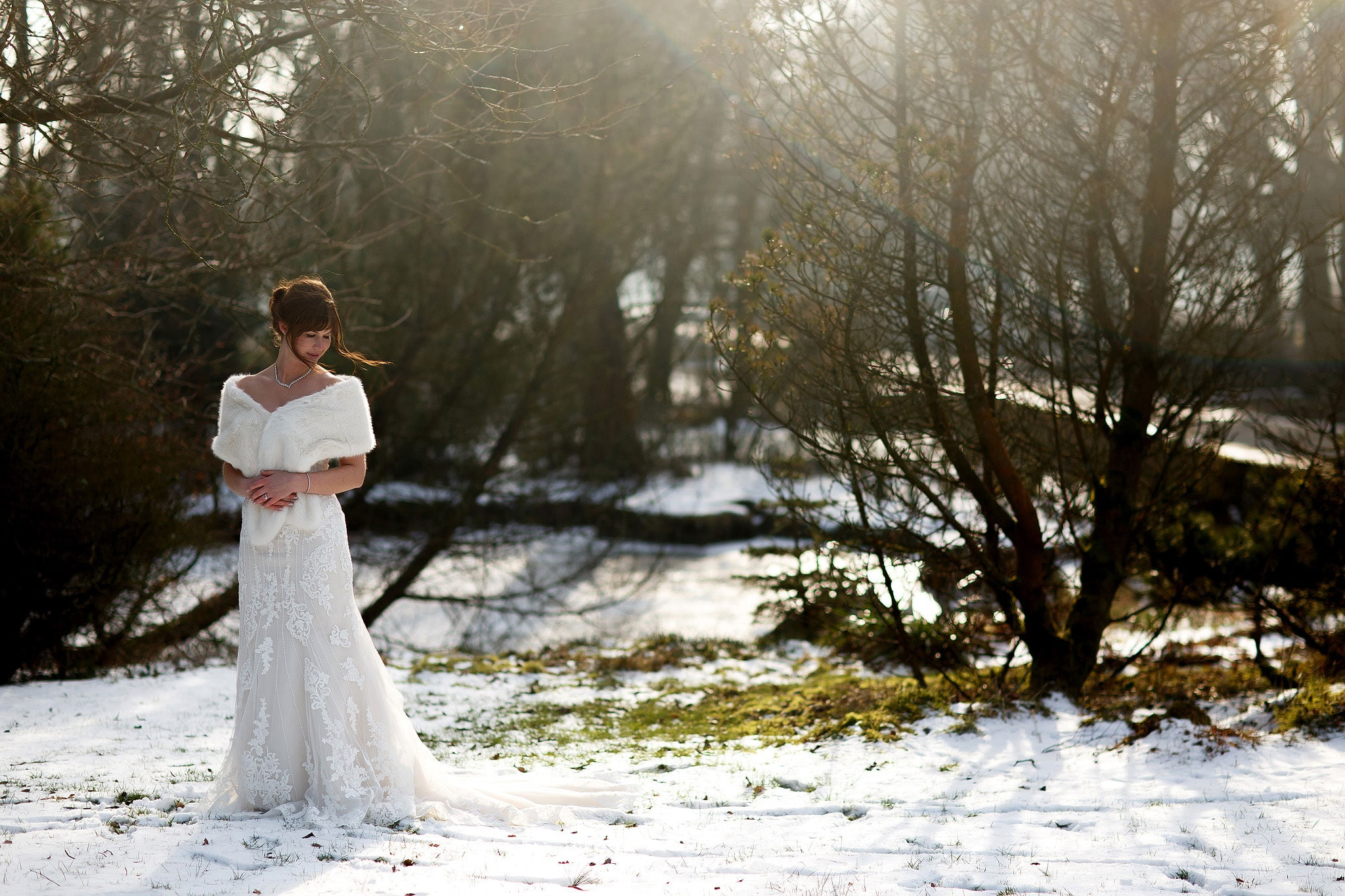 Bridal wearing strapless lace wedding dress and fur shrug looking to the snowy ground during winter wedding at Rivington Hall Barn