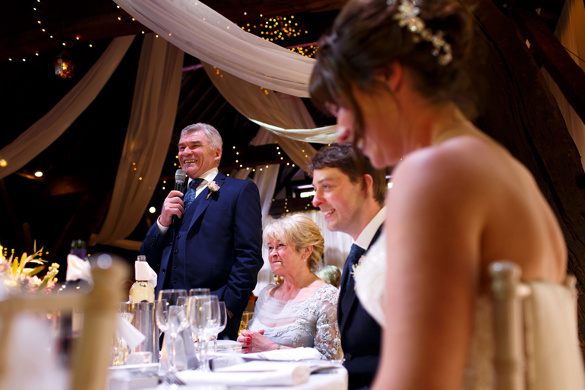 Father of the bride wearing navy suit making his speech during Rivington Hall Barn wedding reception