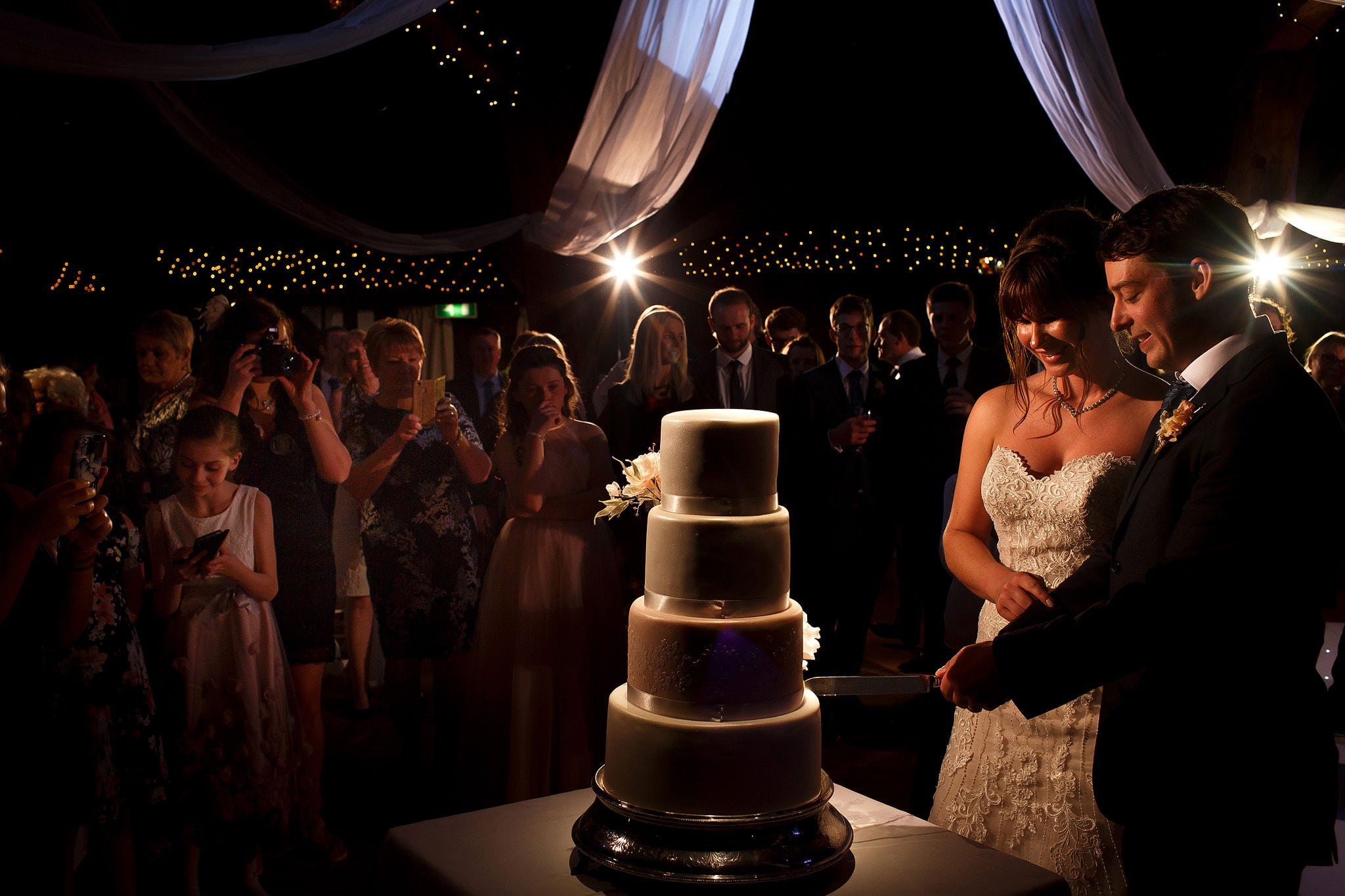 Bride and groom cutting four tier wedding cake in front of all the guests at Rivington Hall Barn wedding reception