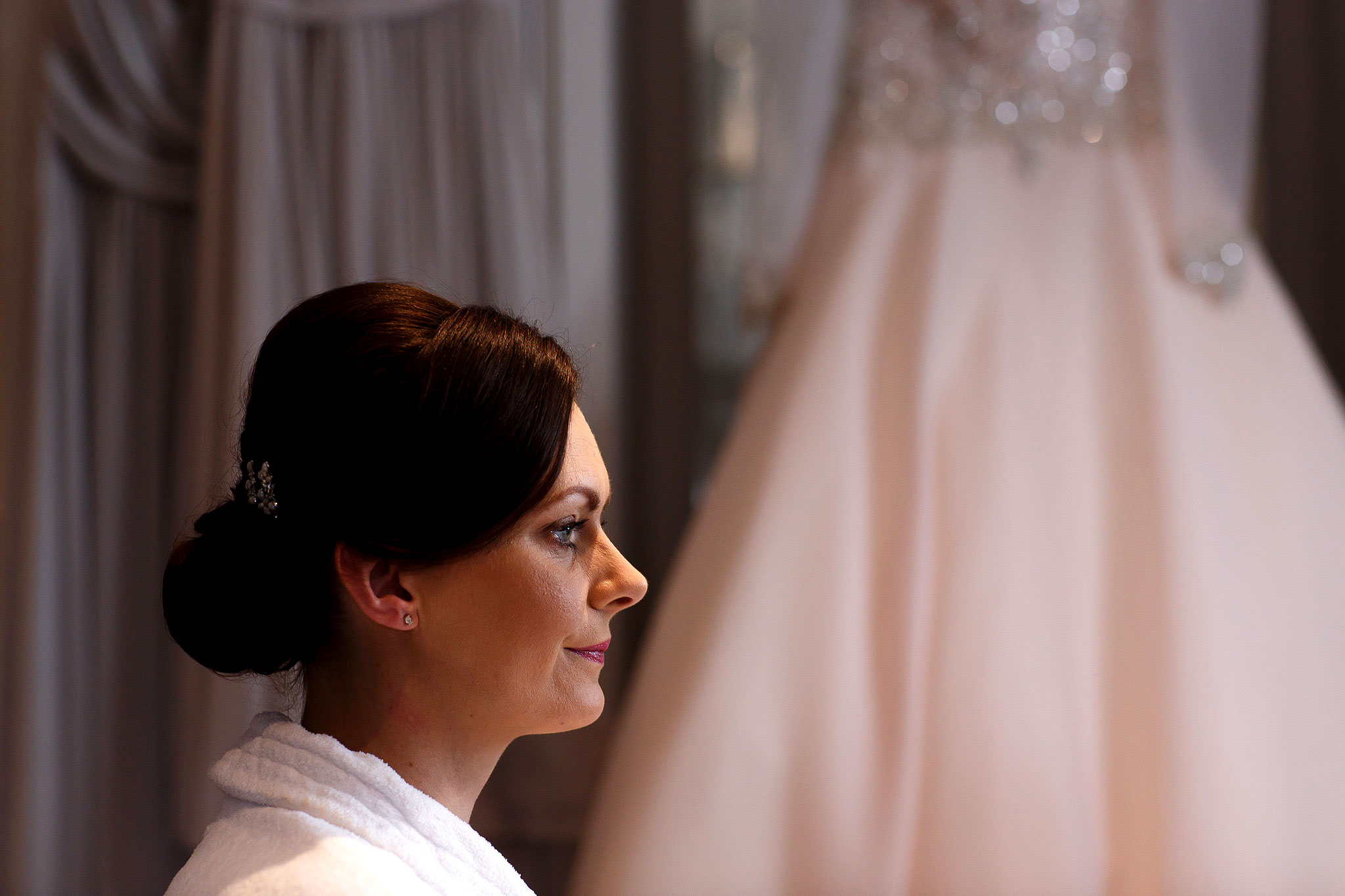 Bride having make up applied with wedding dress in the background in Stanley House Hotel bridal suite