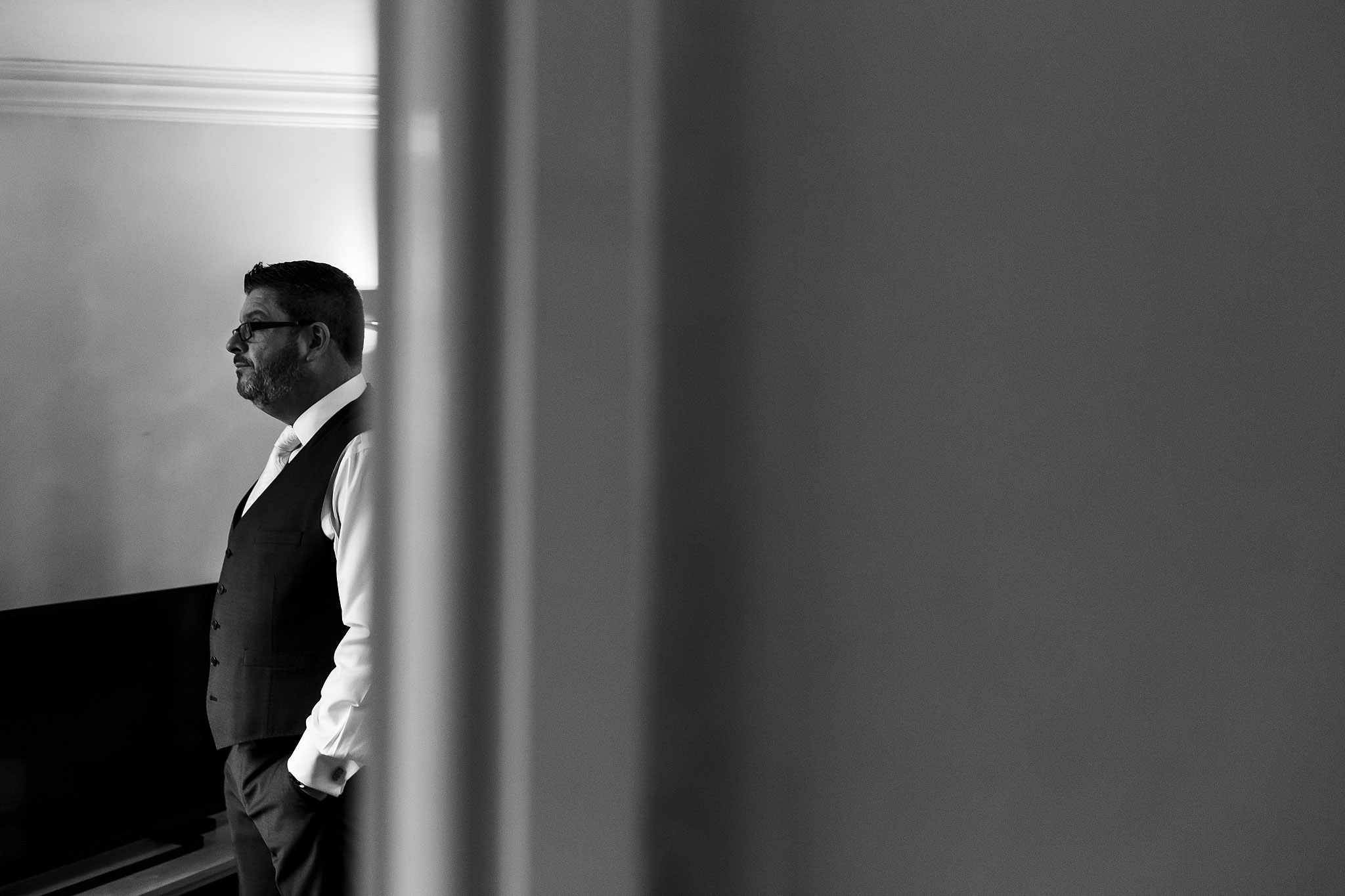 Groom waiting nervously as he looks out the window