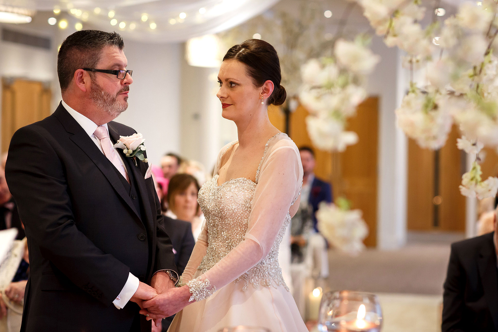 Bride and groom holding hands during wedding ceremony at Stanley House Hotel